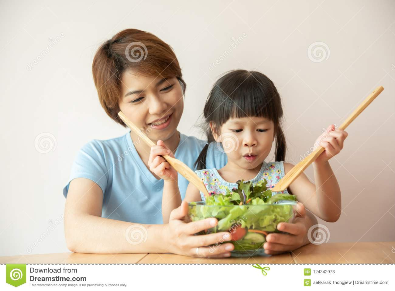 Happy Asian Young Mother and little girl cooking salad.