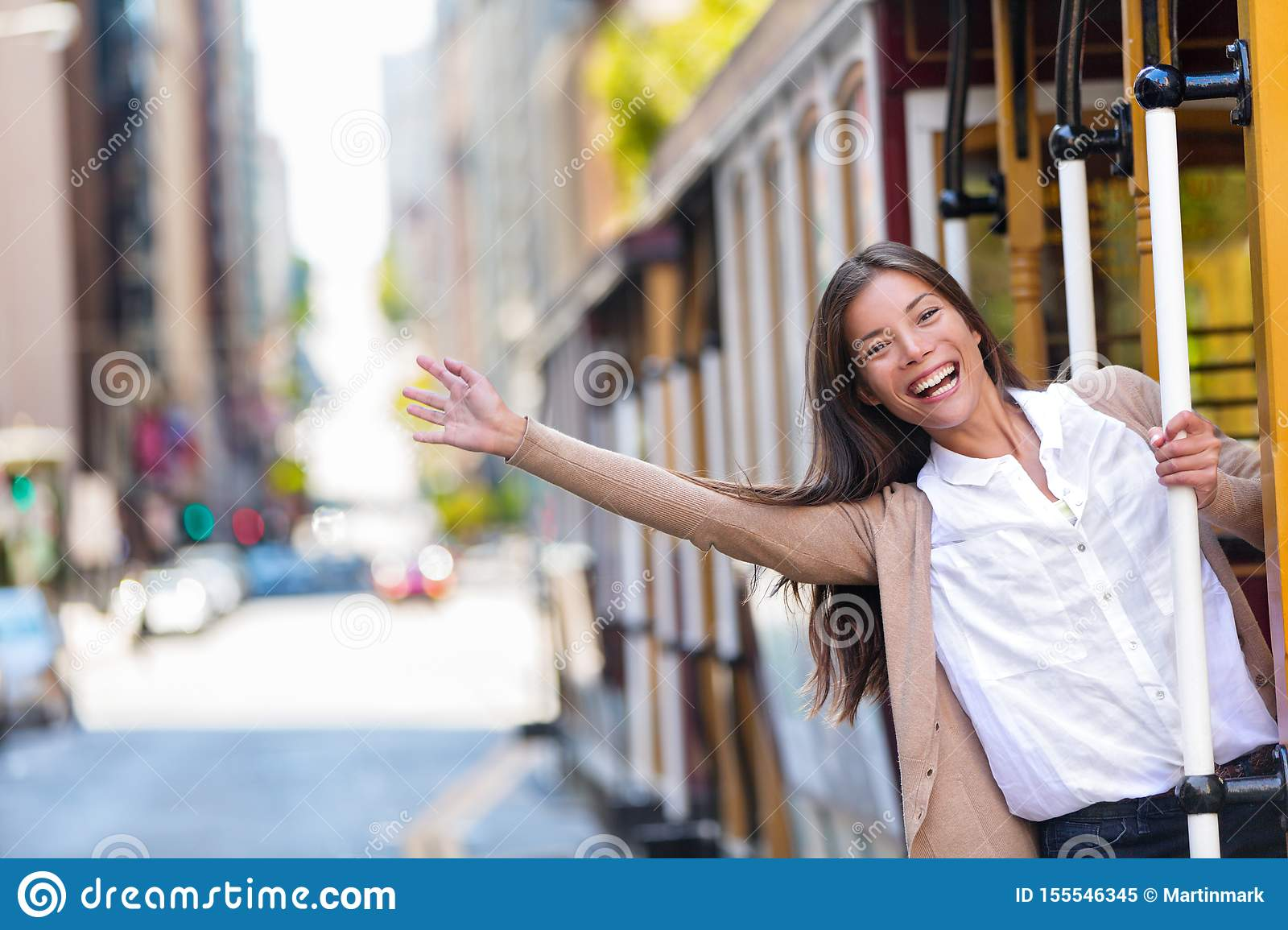 Happy Asian young woman excited having fun riding the popular tourist attraction tramway cable car system in San Francisco city,