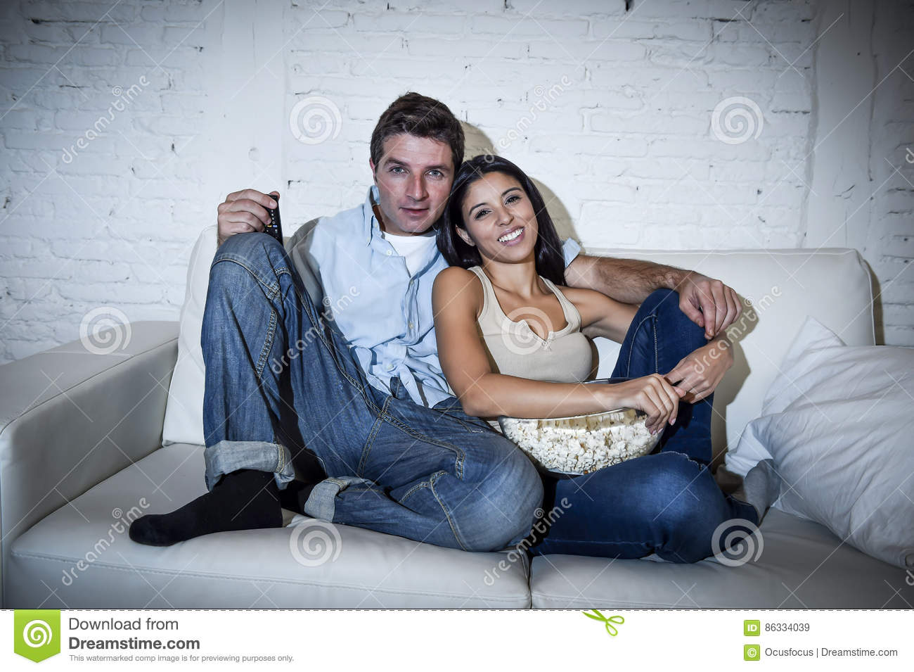 Happy attractive couple having fun at home enjoying watching television relaxed