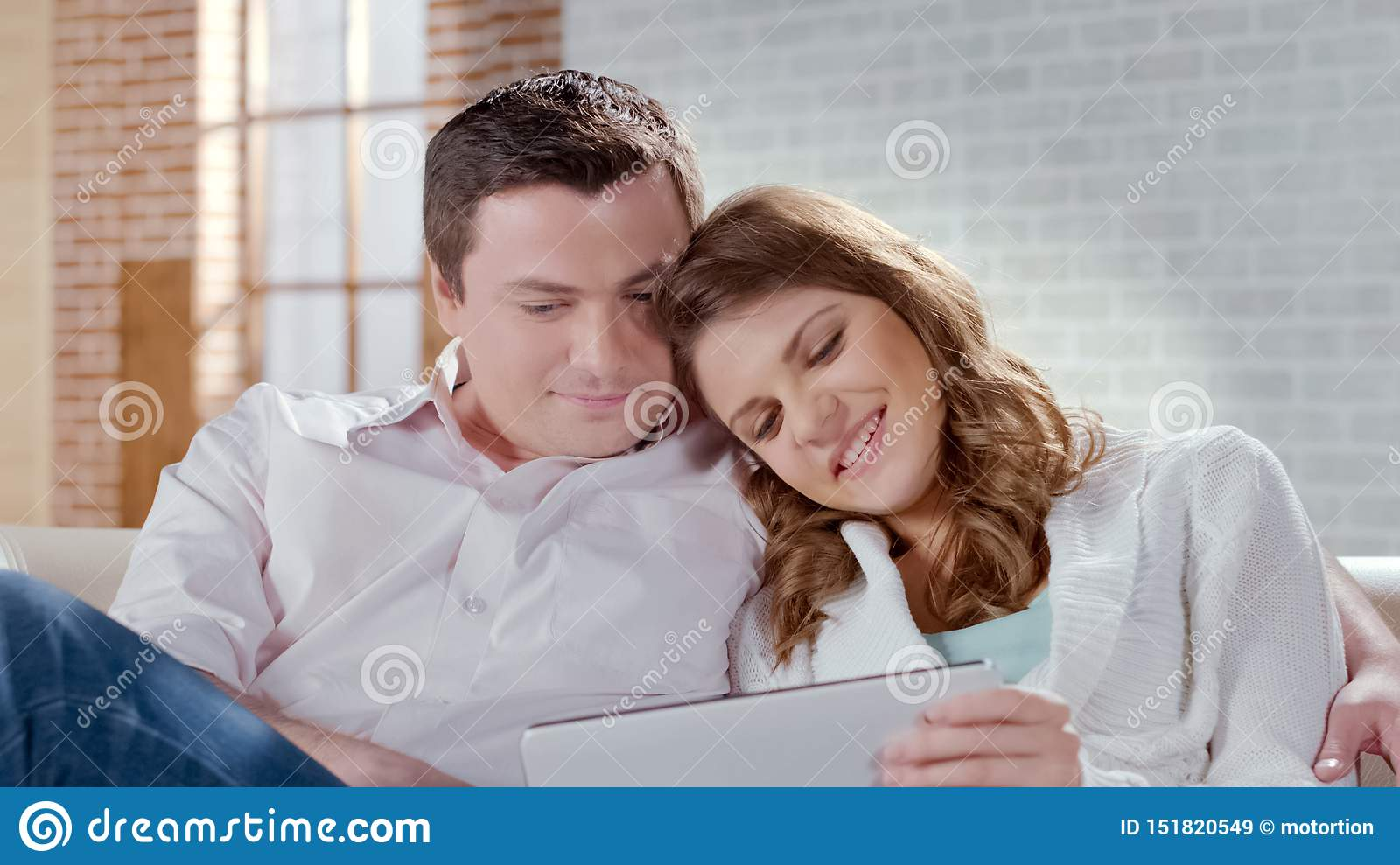 Happy attractive couple viewing photos on tablet, remembering pleasant moments
