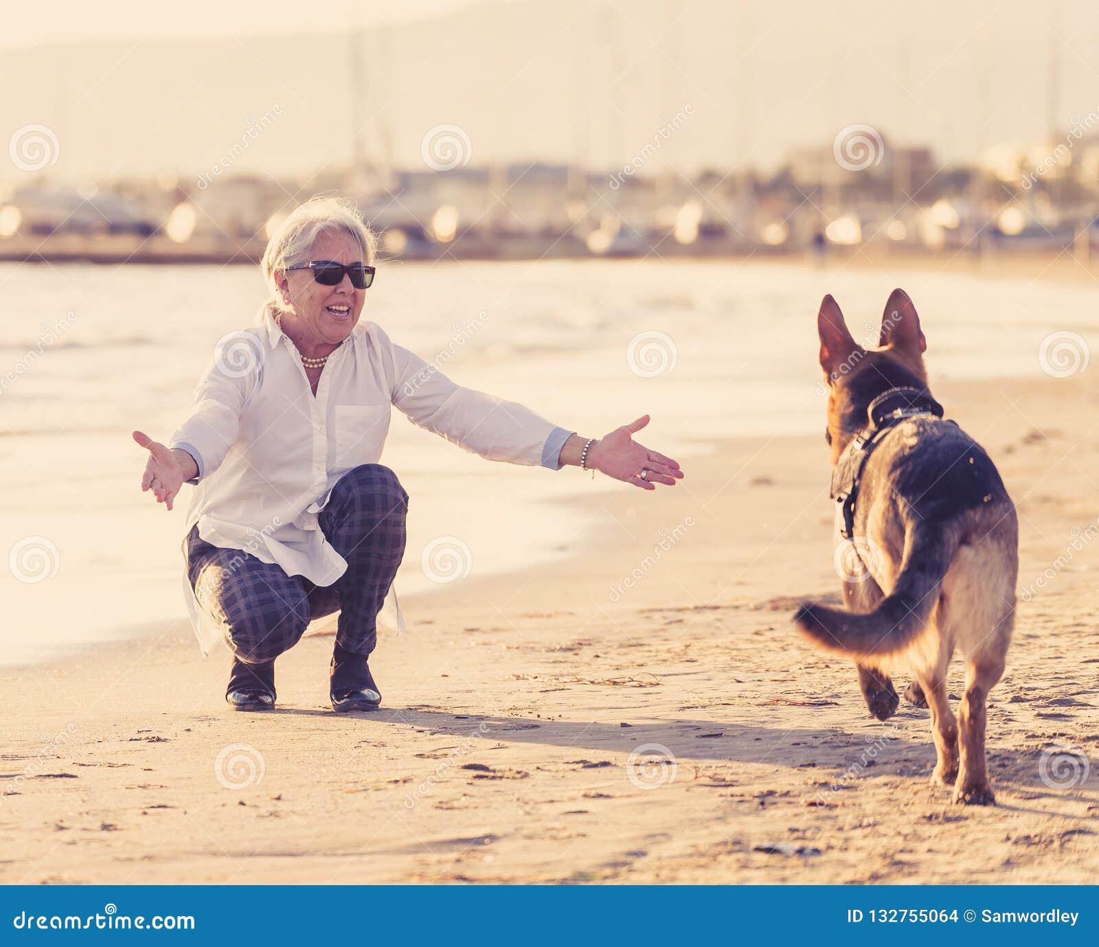 Happy Beautiful Woman Enjoying At Beach Stock Photo: Happy Attractive Senior Woman With Her German Shepard Dog