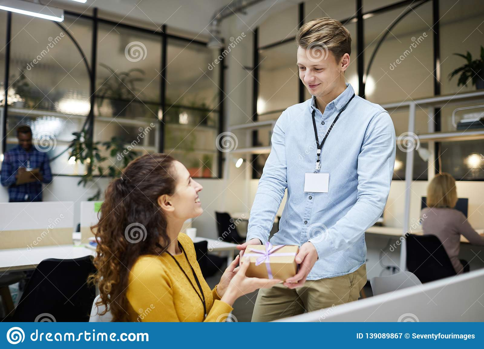 Happy Attractive Young Lady With Curly Hair Sitting At Table And Accepting Gift From Colleague Badge On Neck Birthday Concept