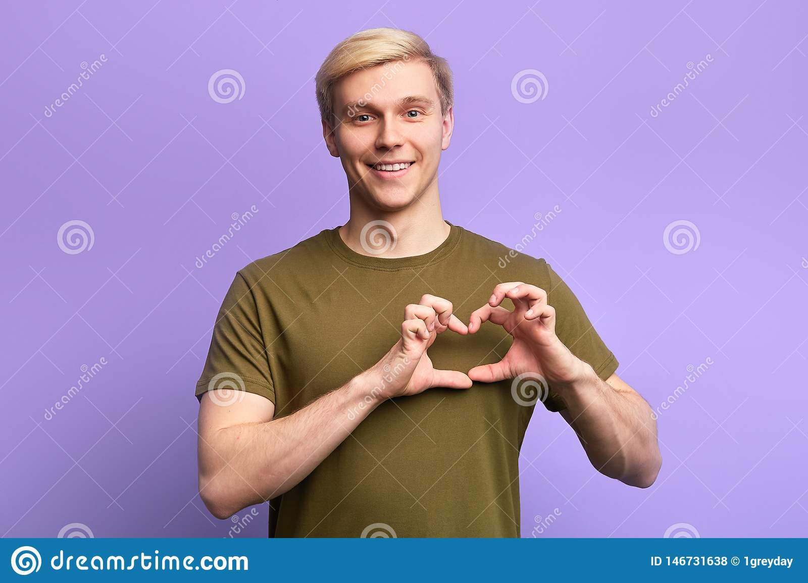 Happy attractive young man, holding hands in heart gesture ,