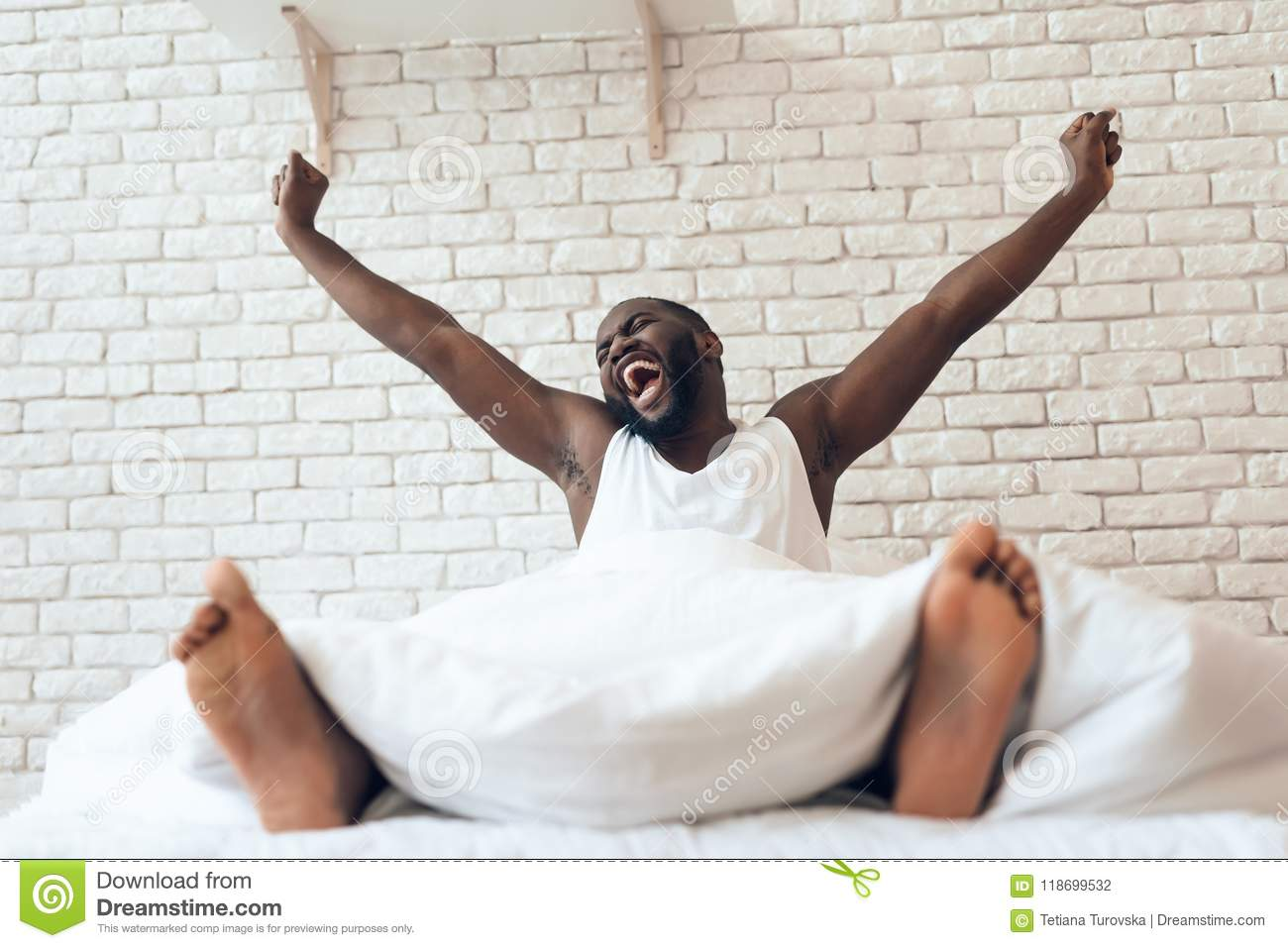 Happy awakened man is stretched out in bed.