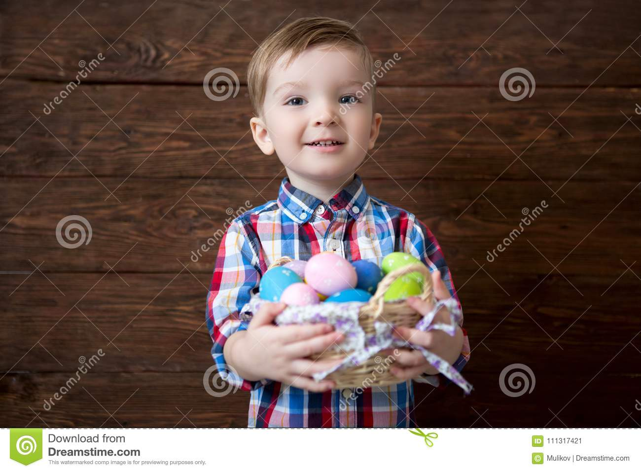 Happy baby boy with a basket of easter eggs on wooden background