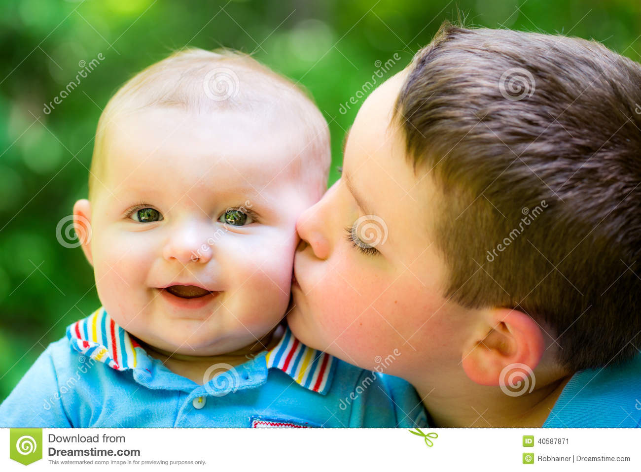 Happy baby boy kissed by his brother