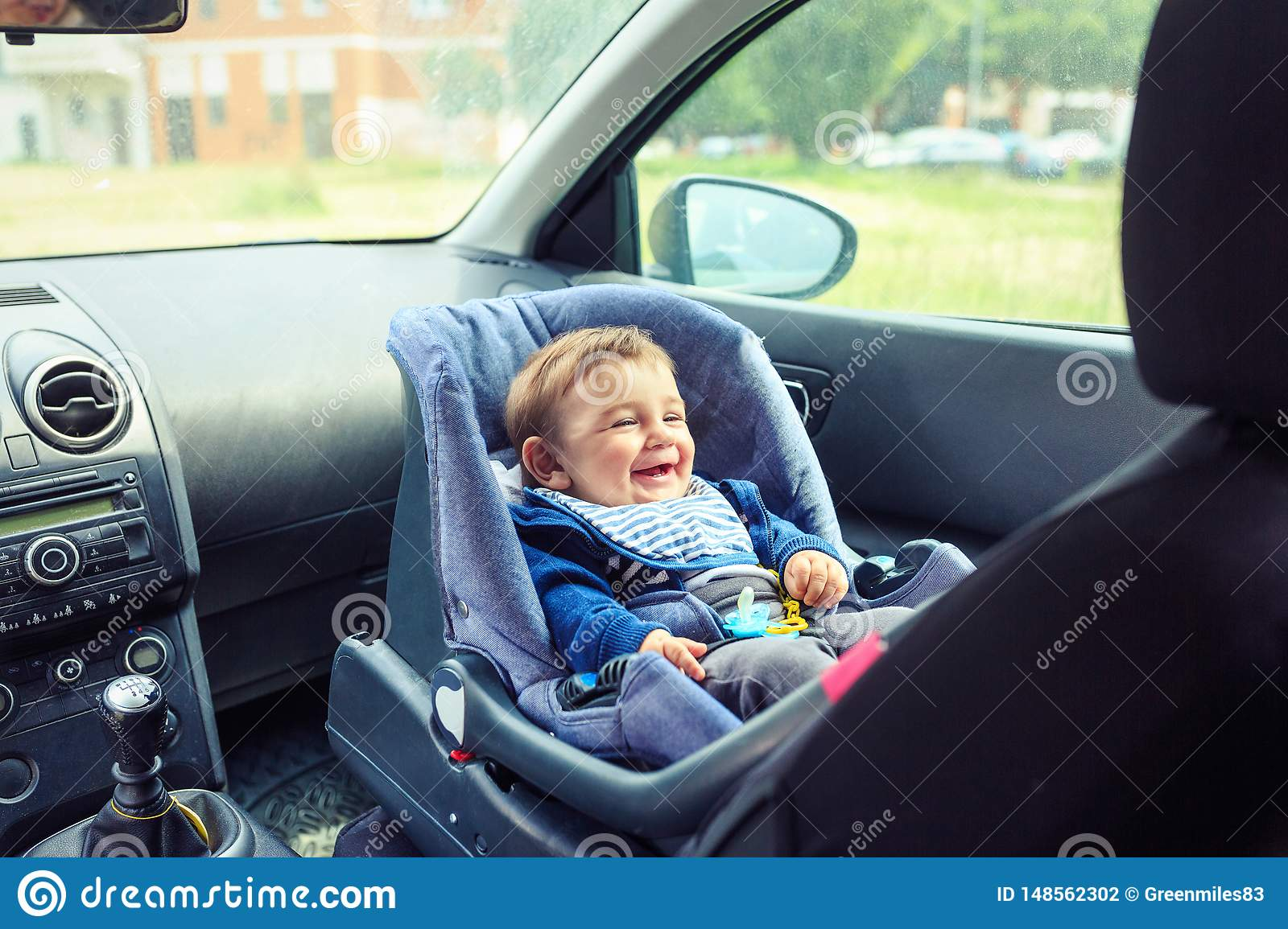 Happy baby boy sitting in a car in safety chair