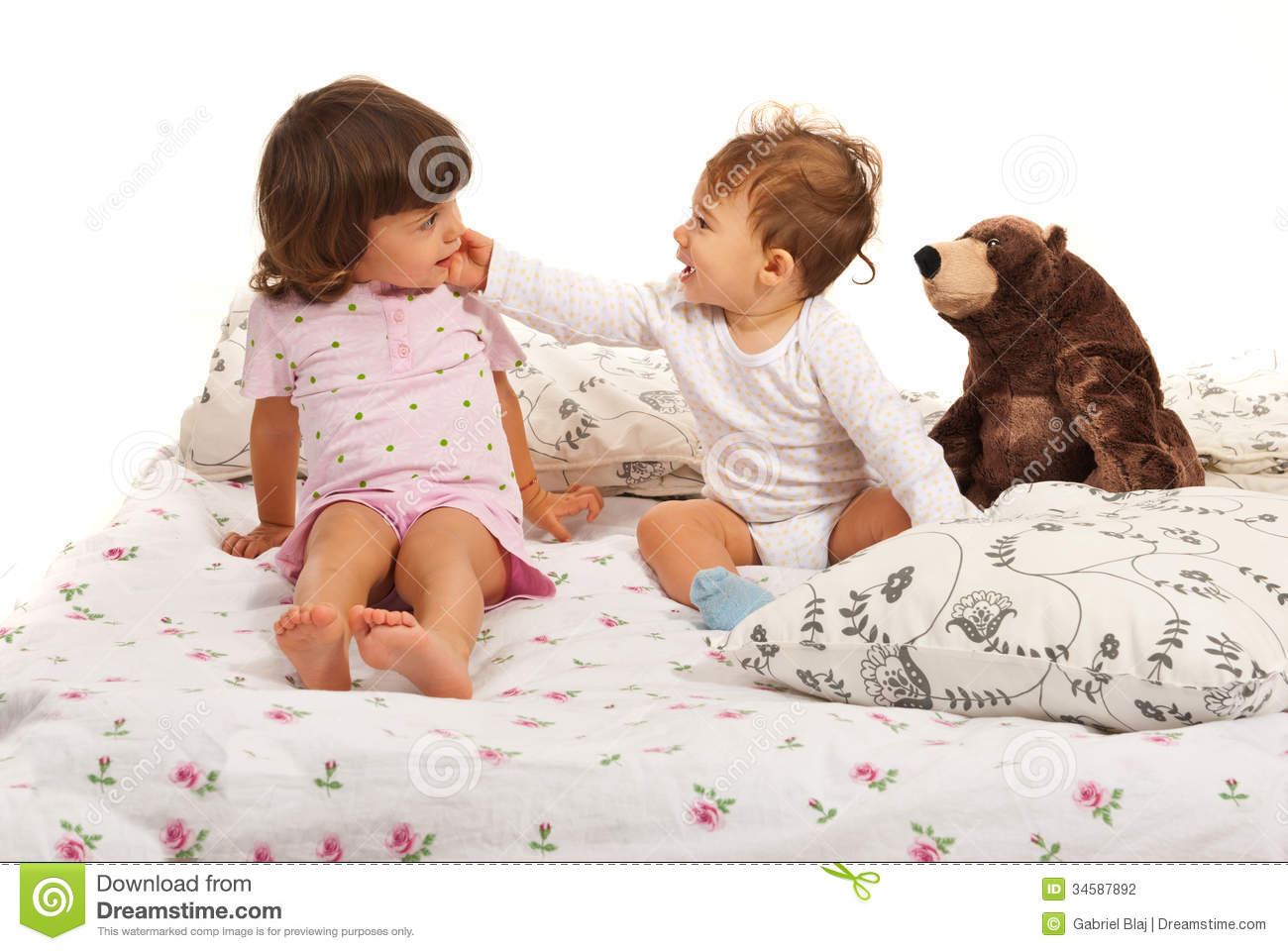 Happy baby boy touching toddler girl stock photo image for Boys and girls in bed