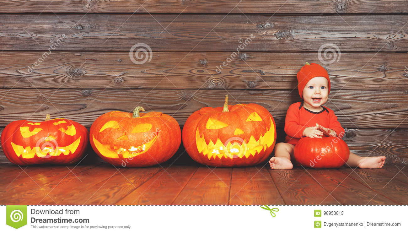 Happy baby in costume for Halloween with pumpkins on wooden back