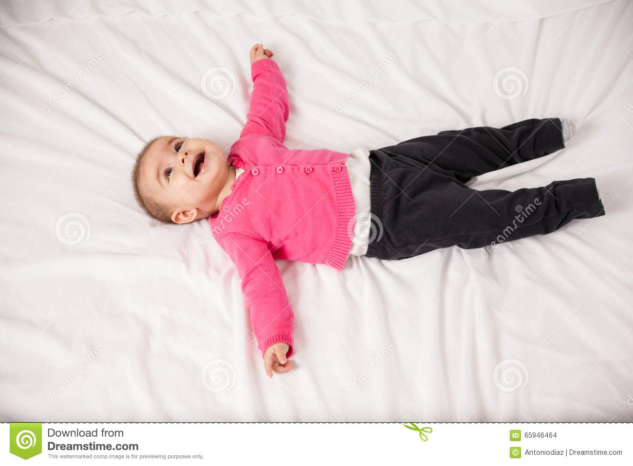 Happy Baby Girl Lying On A Bed Stock Photo - Image 65946464-6004