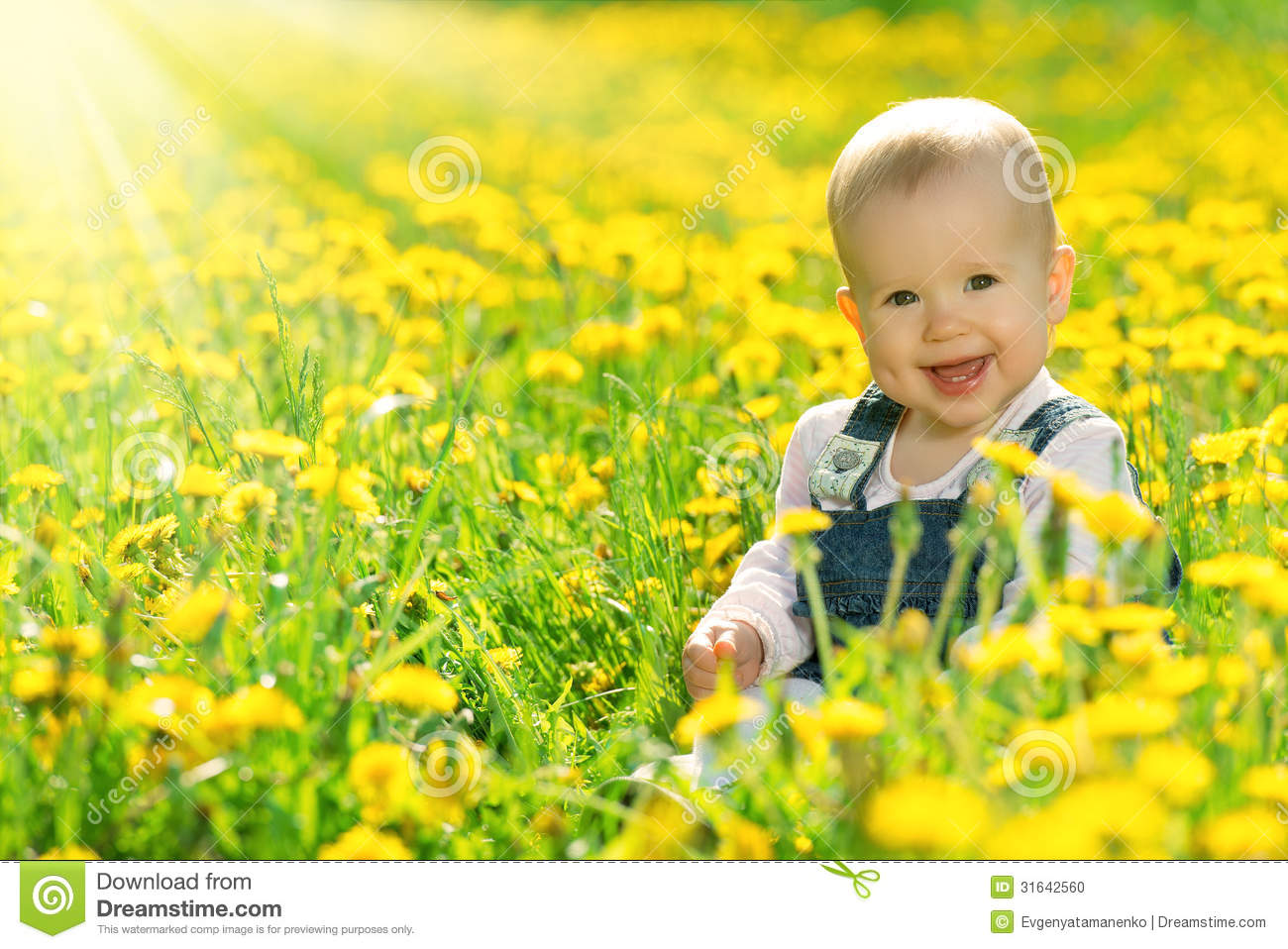Happy Baby Girl On Meadow With Yellow Flowers On The