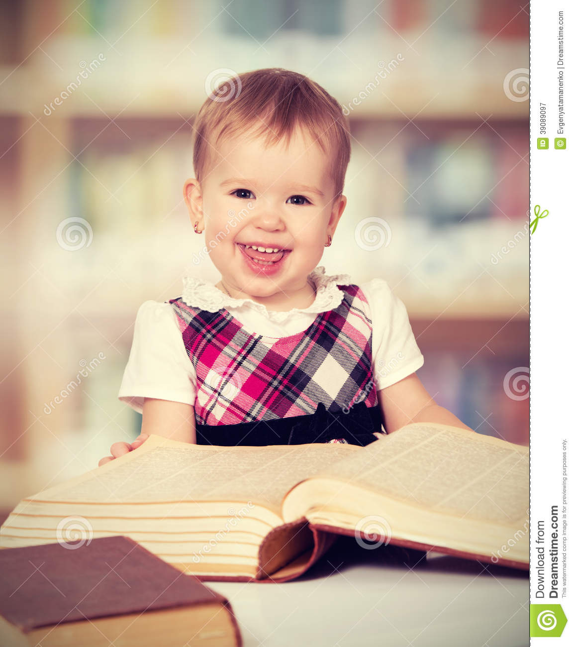 Happy Baby Girl Reading A Book In A Library Stock Photo ... Cute Happy Baby Girl