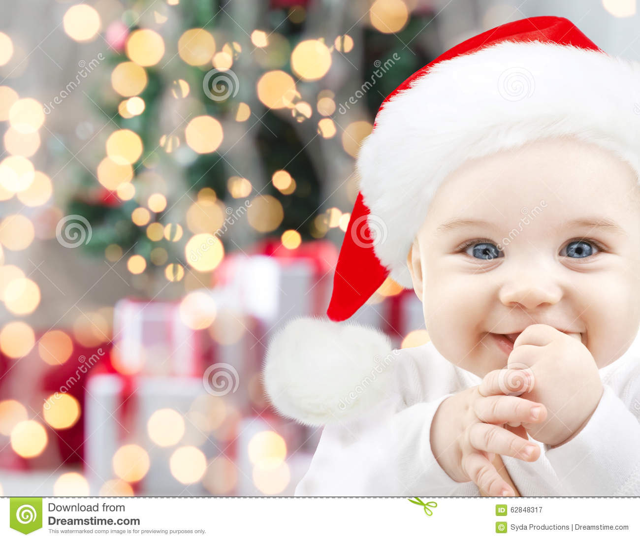 Happy Baby In Santa Hat Over Christmas Lights Stock Image