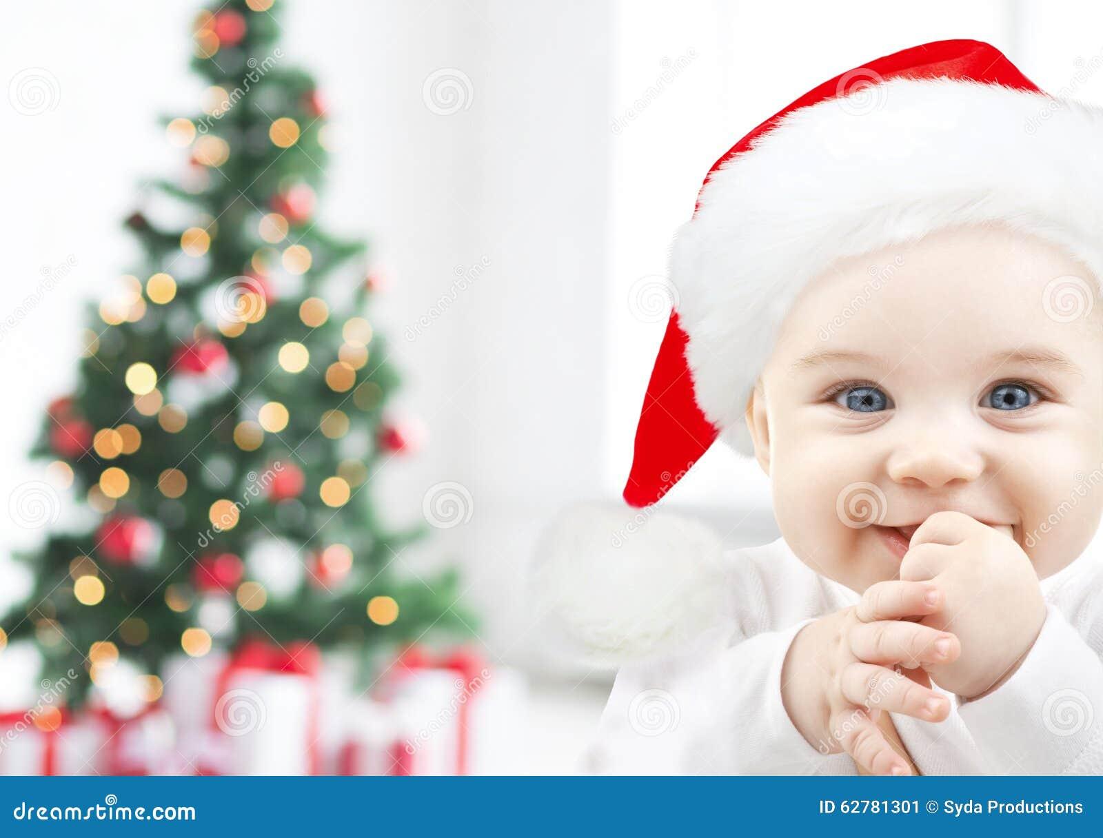 Happy Baby In Santa Hat Over Christmas Tree Lights Stock