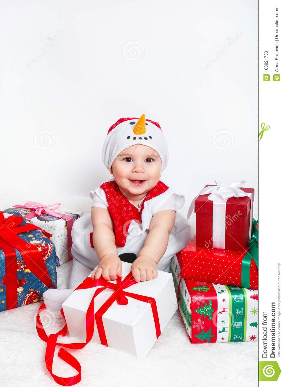 happy baby in snowman costume with christmas present gift boxs
