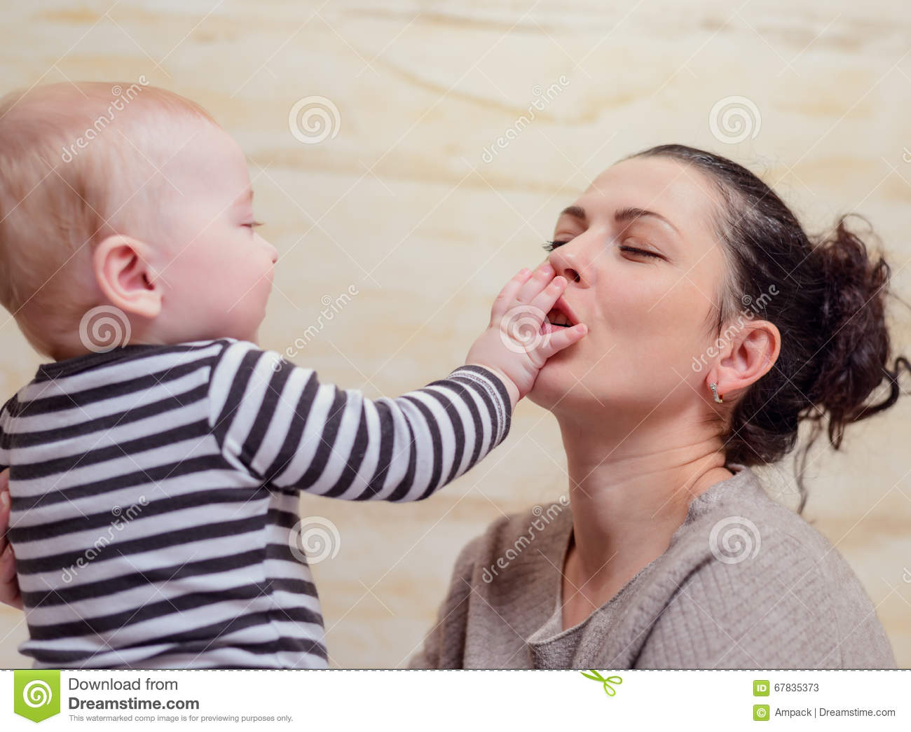 Happy baby touching face of woman
