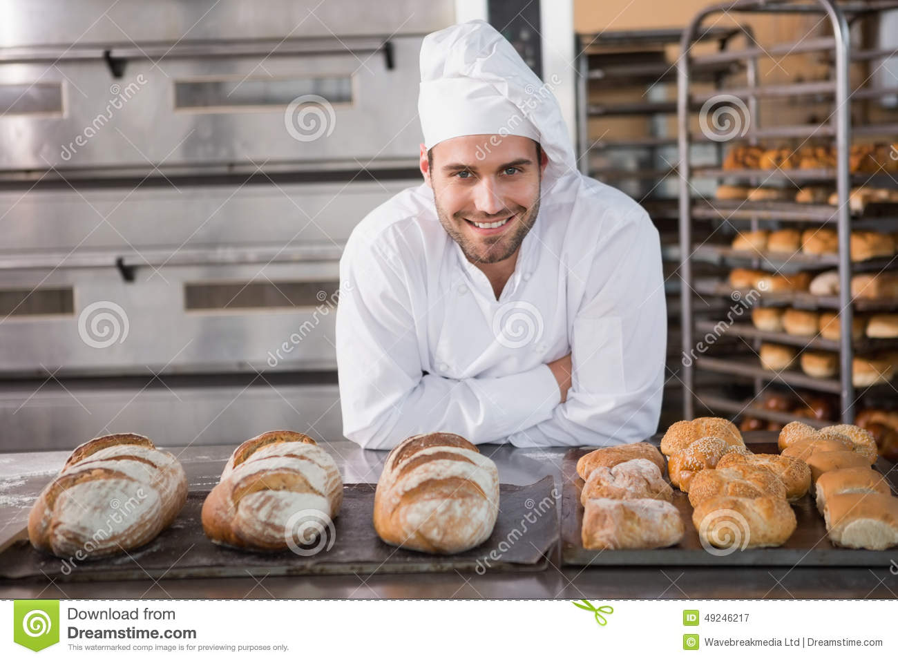 Happy baker standing near tray with bread