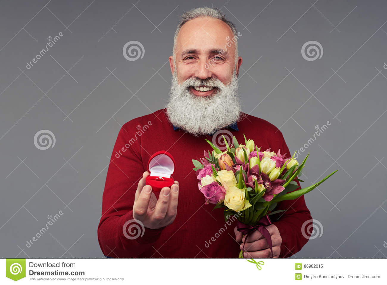 Happy bearded man holding bouquet of tulips and gift bo