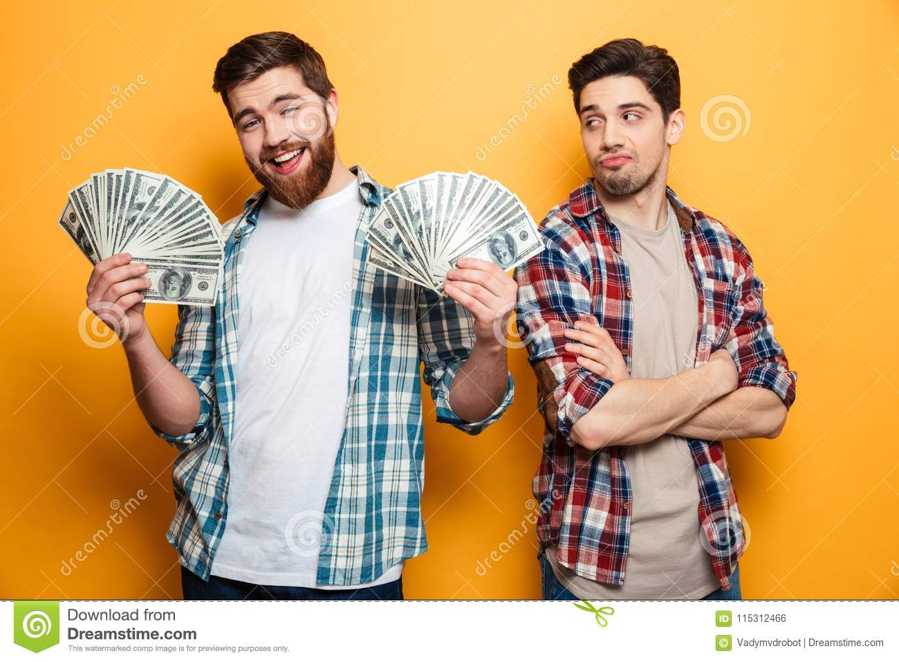 Happy bearded man holding money and looking at the camera
