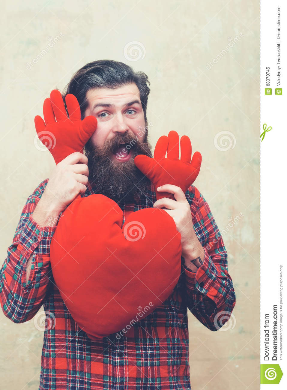 Happy bearded man holding red heart shape toy with hands