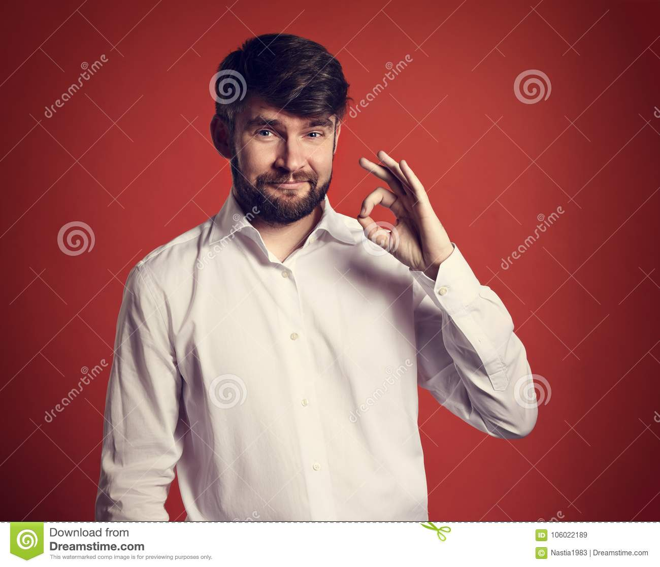 72823c4c2c68 Happy bearded smiling business man showing okay sign in fashion white style  shirt on red background. Closeup toned portrait