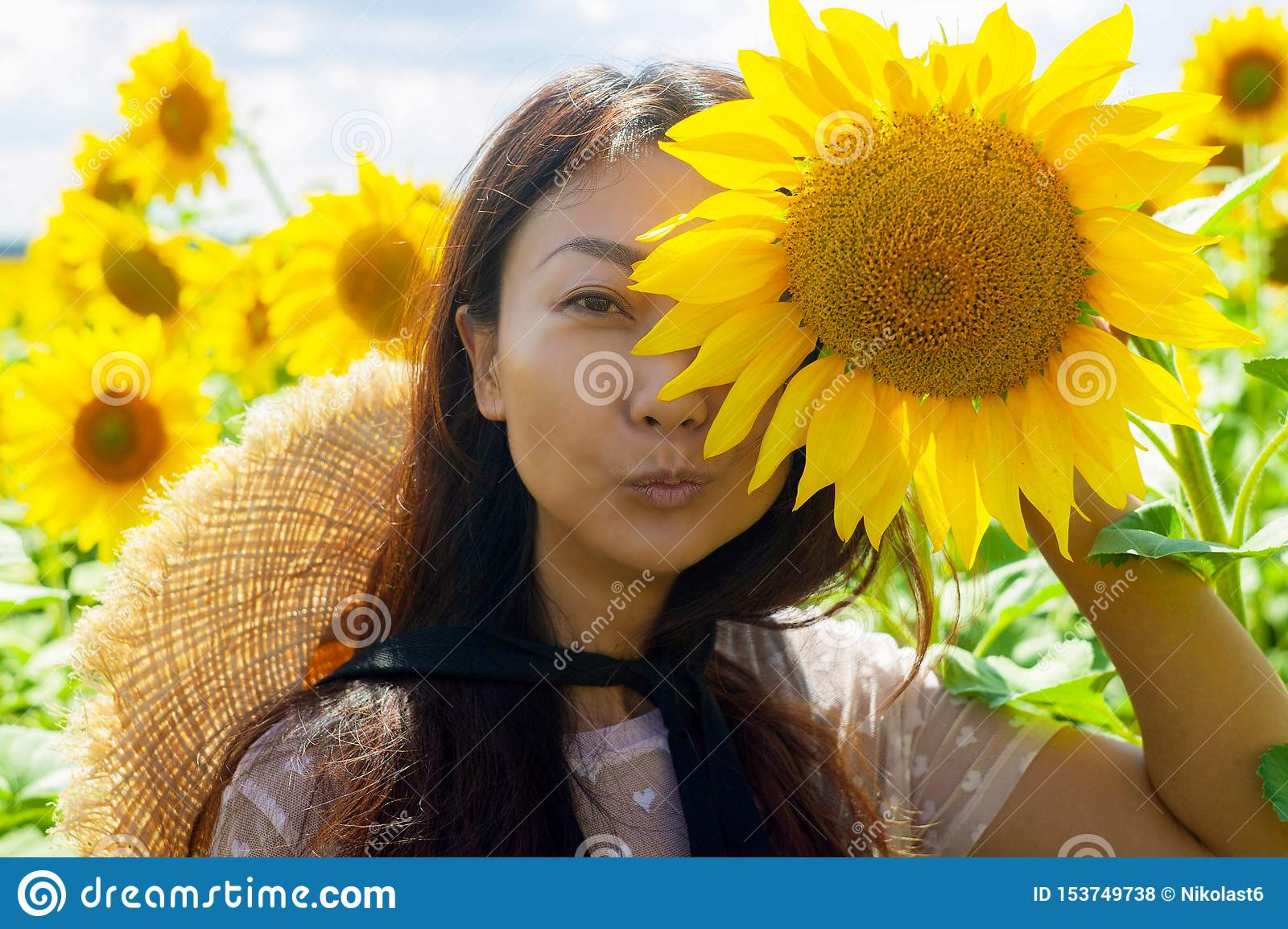 Happy beautiful asian woman with straw hat in sunflower field.