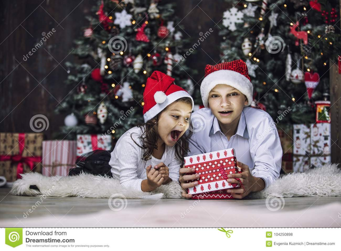 Happy beautiful children boy and girl with gifts to celebrate Christmas and new year together