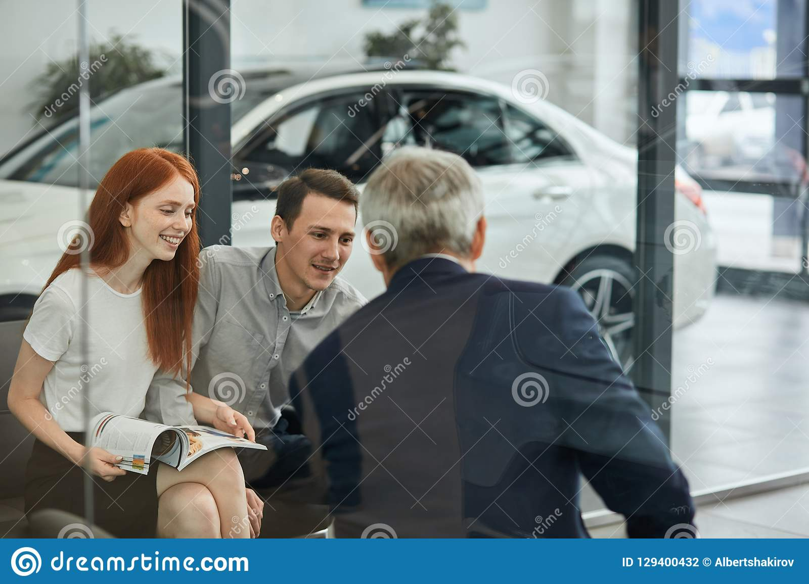Happy beautiful couple is buying a new car at dealership. Family council