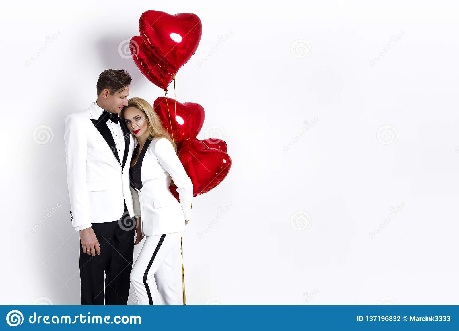 Happy beautiful couple posing on white background and holding balloons heart. Valentine`s day.