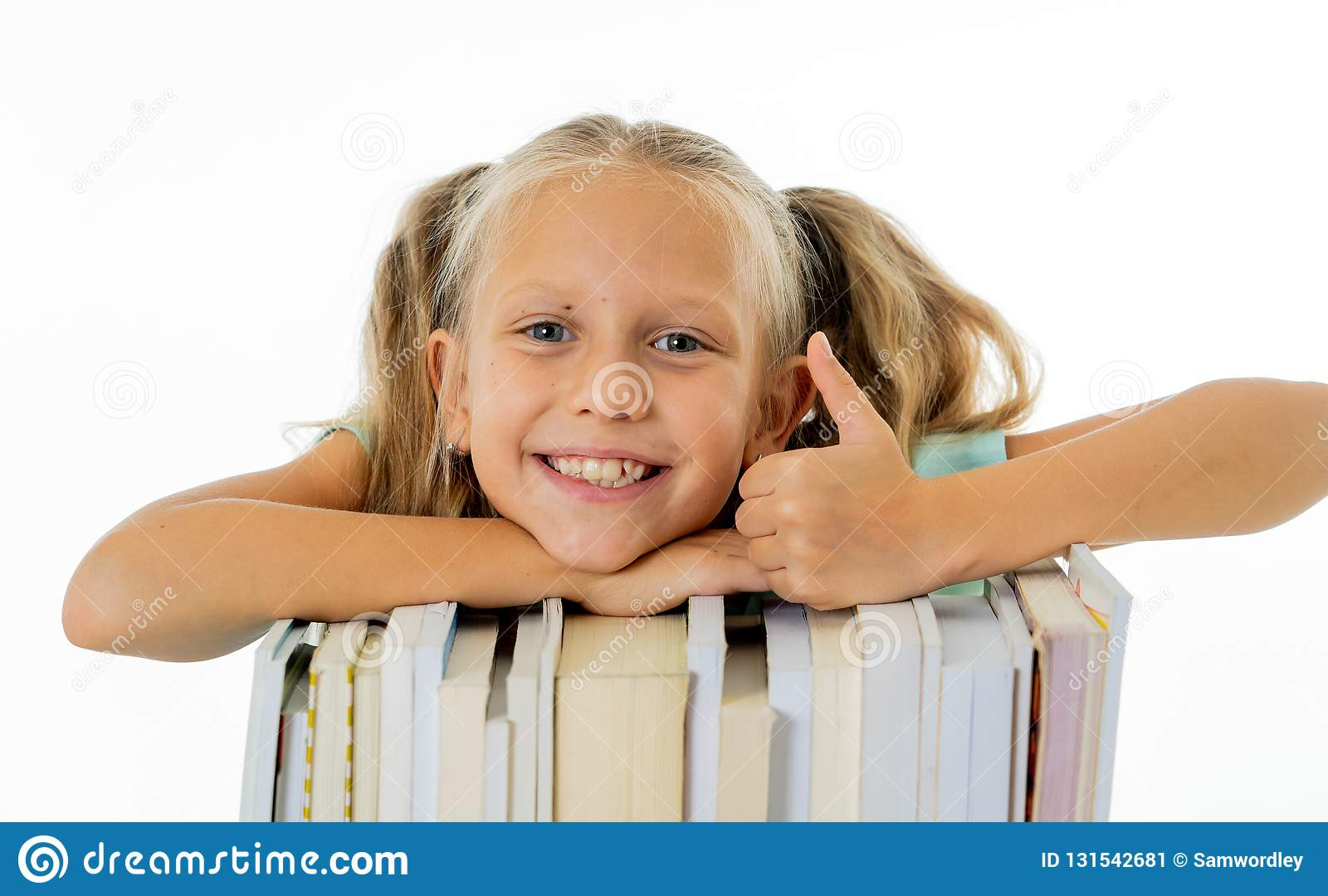 Happy beautiful cute with blond hair little schoolgirl likes studying and reading books in creative education concept with Back to