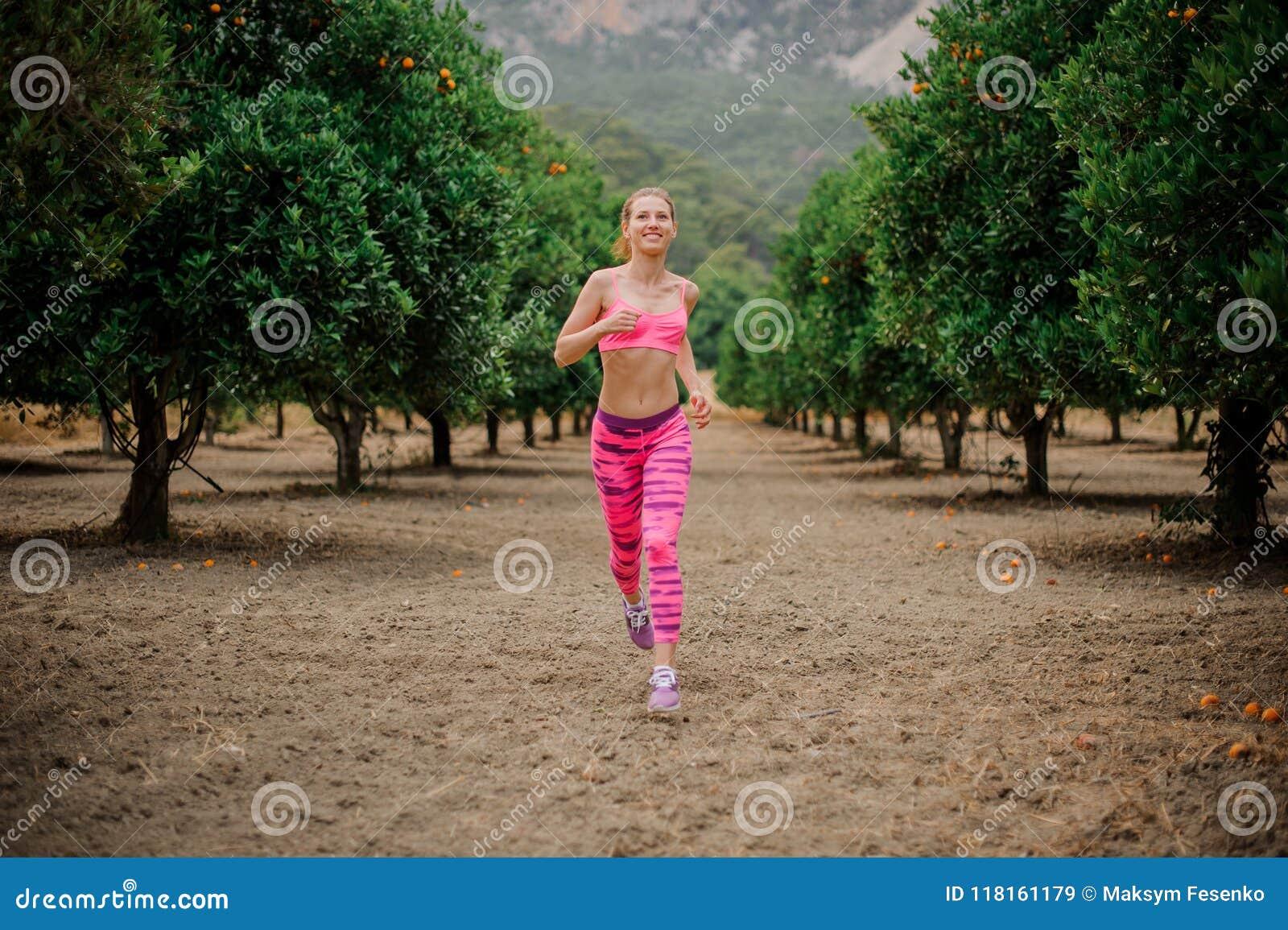 Happy beautiful girl running among orange trees
