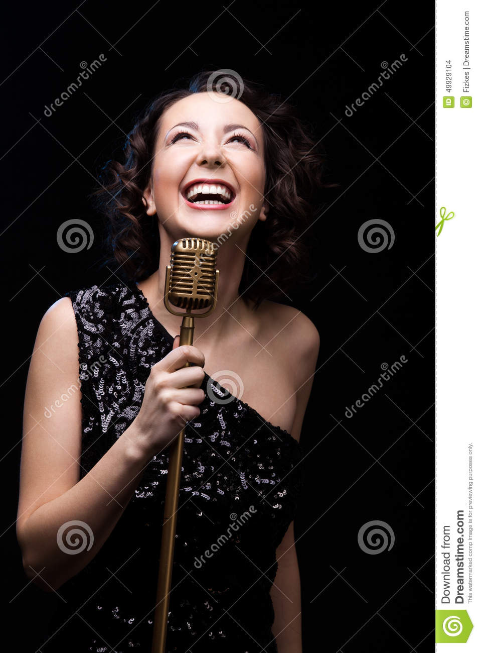 Happy beautiful girl singer laughing holding retro microphone