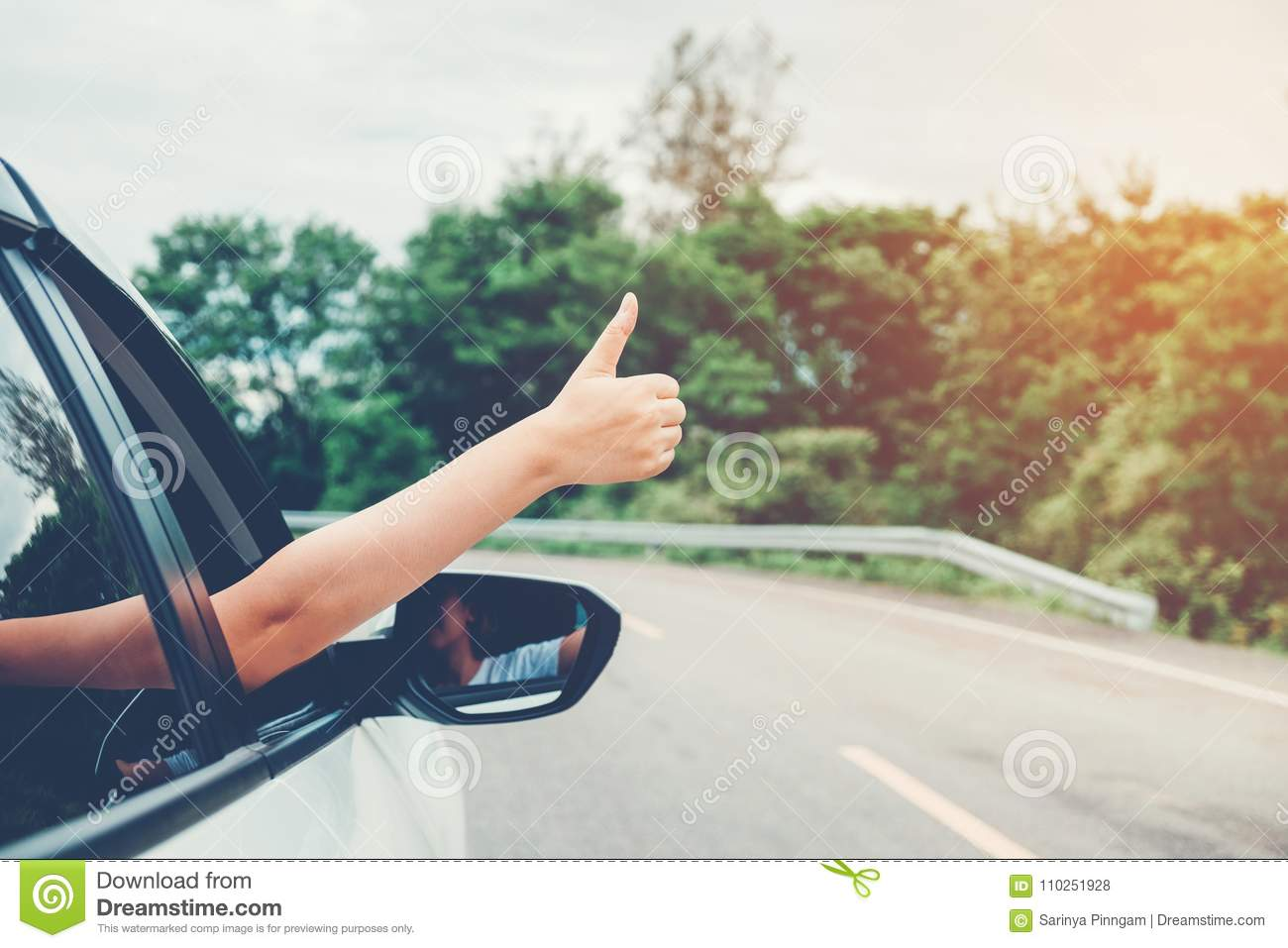Happy beautiful girl traveling in a hatchback car