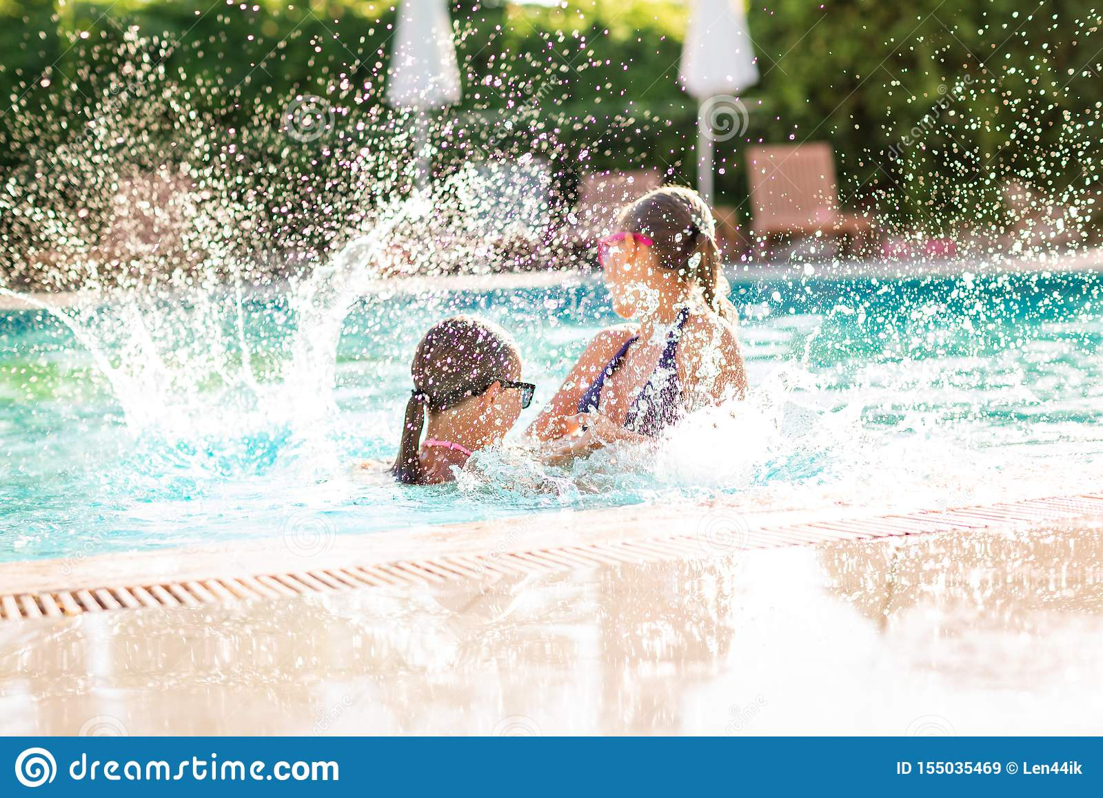 Happy beautiful girls having fun at the pool