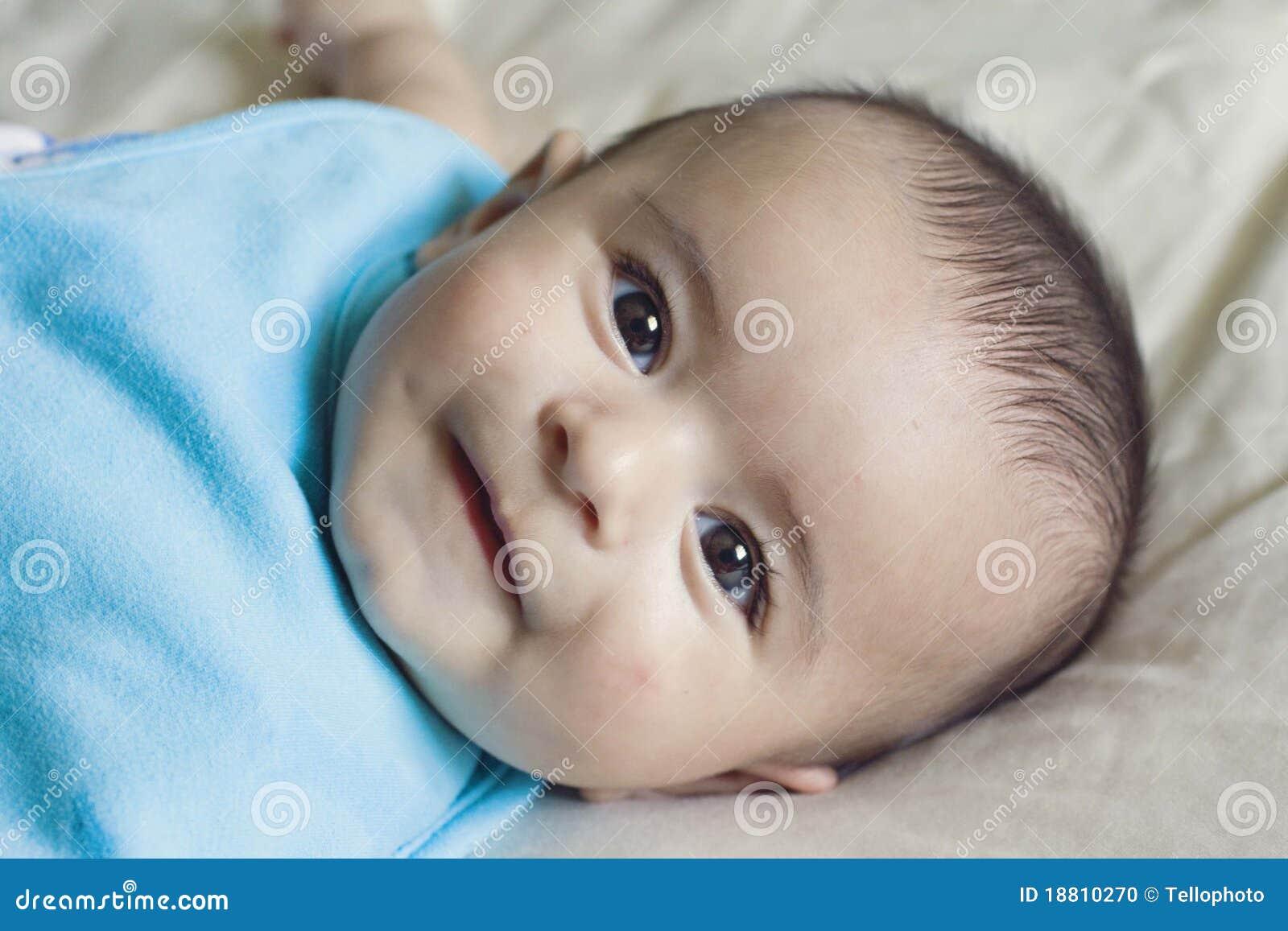 Happy beautiful hispanic baby boy cooing stock photo