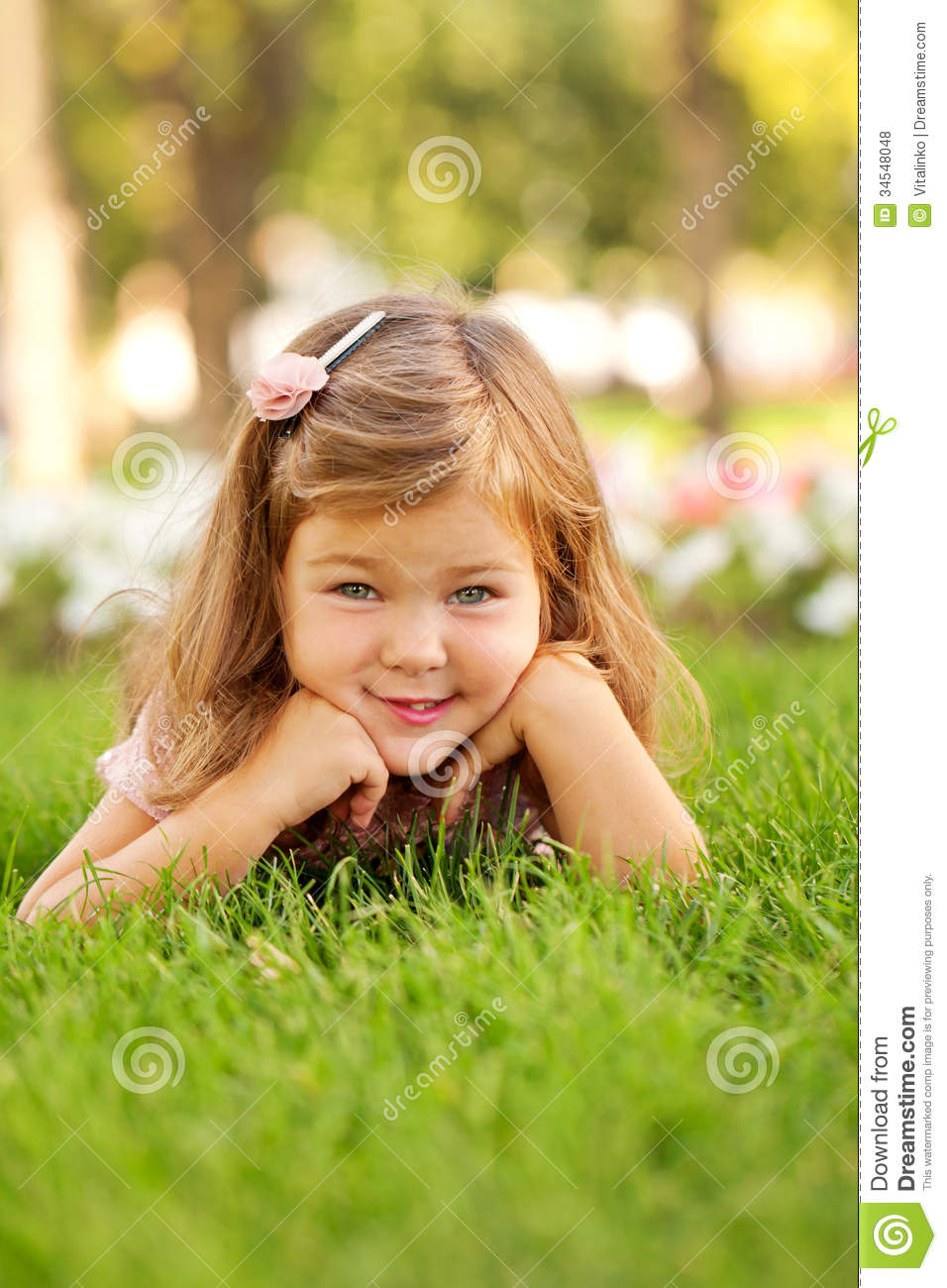 Happy Beautiful Little Girl Lying On The Grass Stock Photo