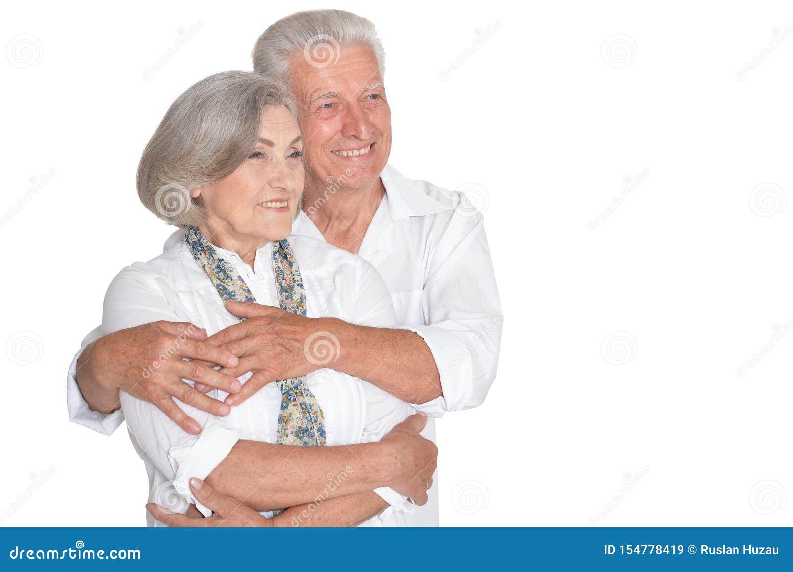 Happy beautiful senior couple huging and posing on white background