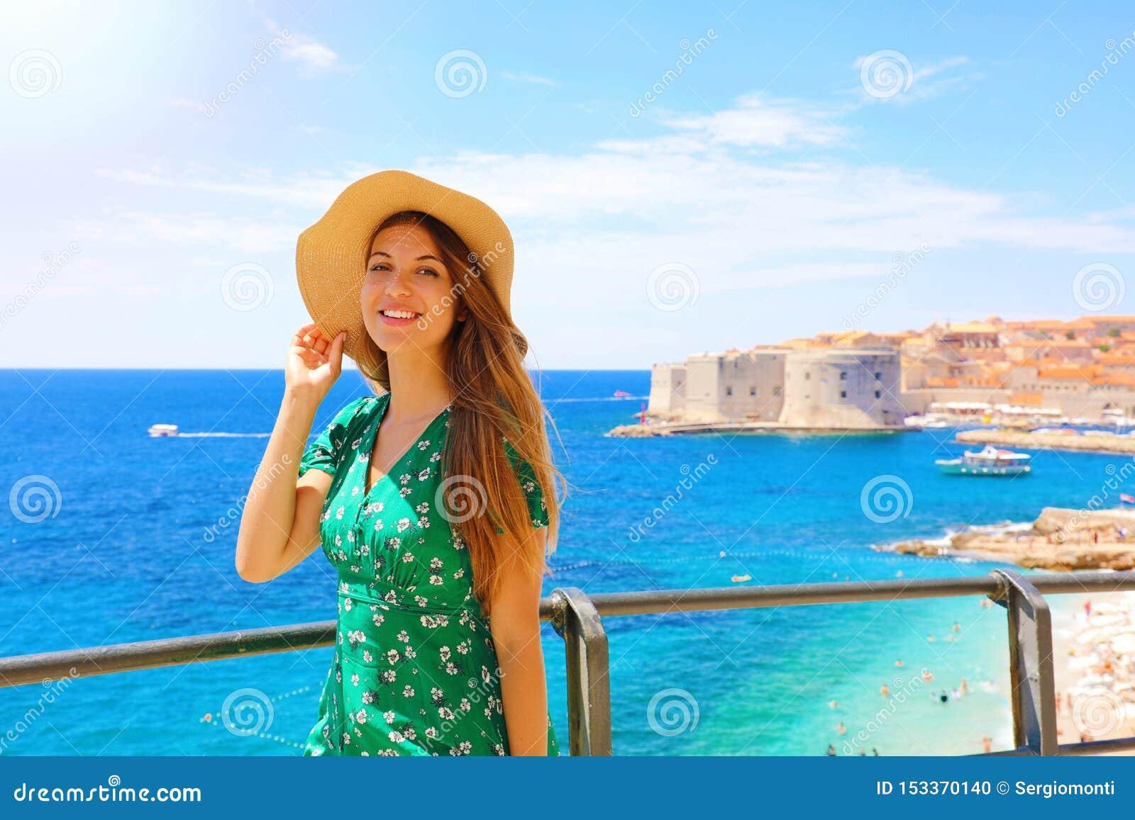 Happy beautiful woman enjoying her cruise in Mediterranean Sea. Smiling traveler girl enjoying her summer holidays in Dubrovnik,