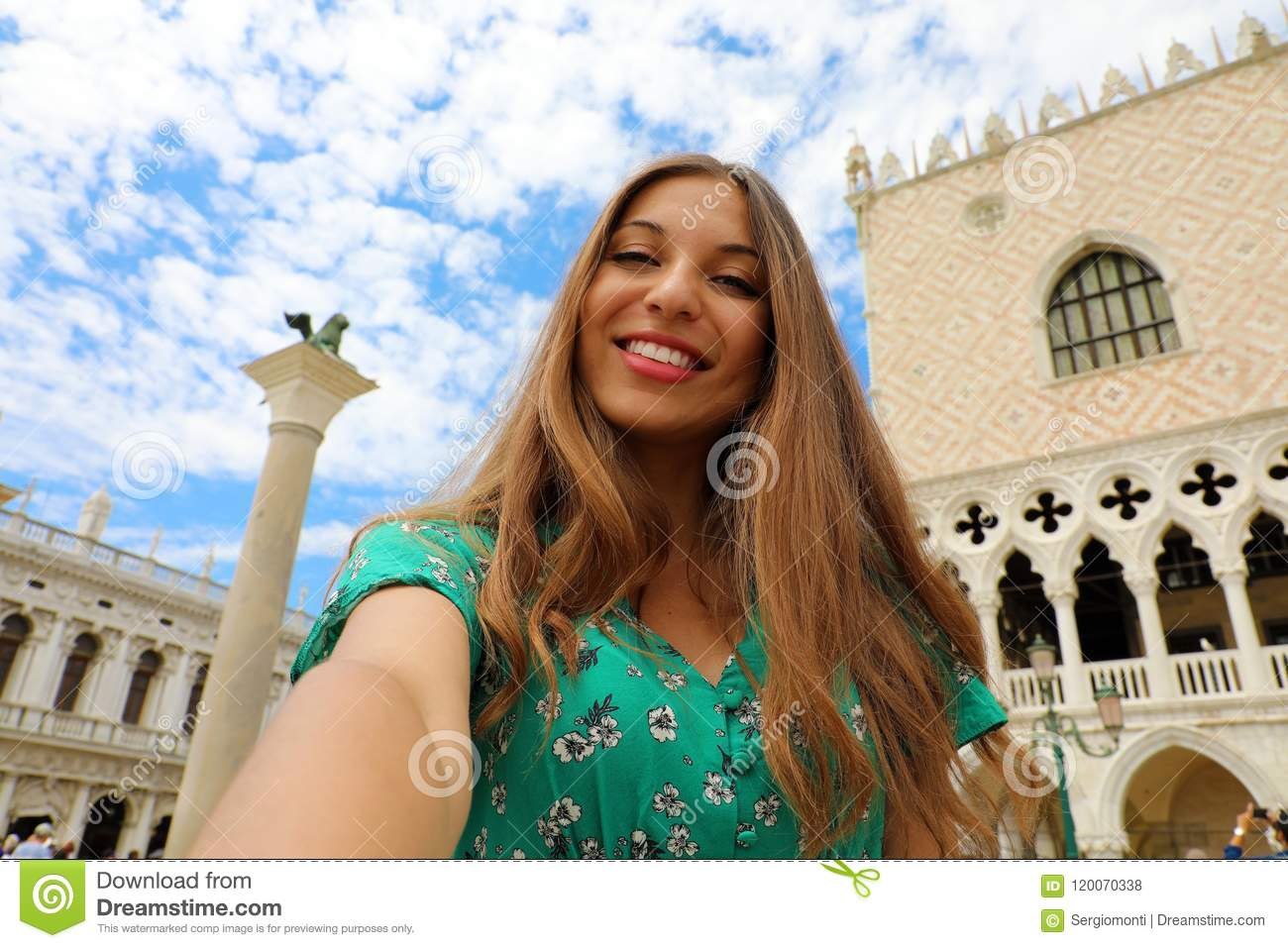 Happy beautiful woman taking selfie photo in Venice with white clouds in the sky. Tourist girl smiling at camera
