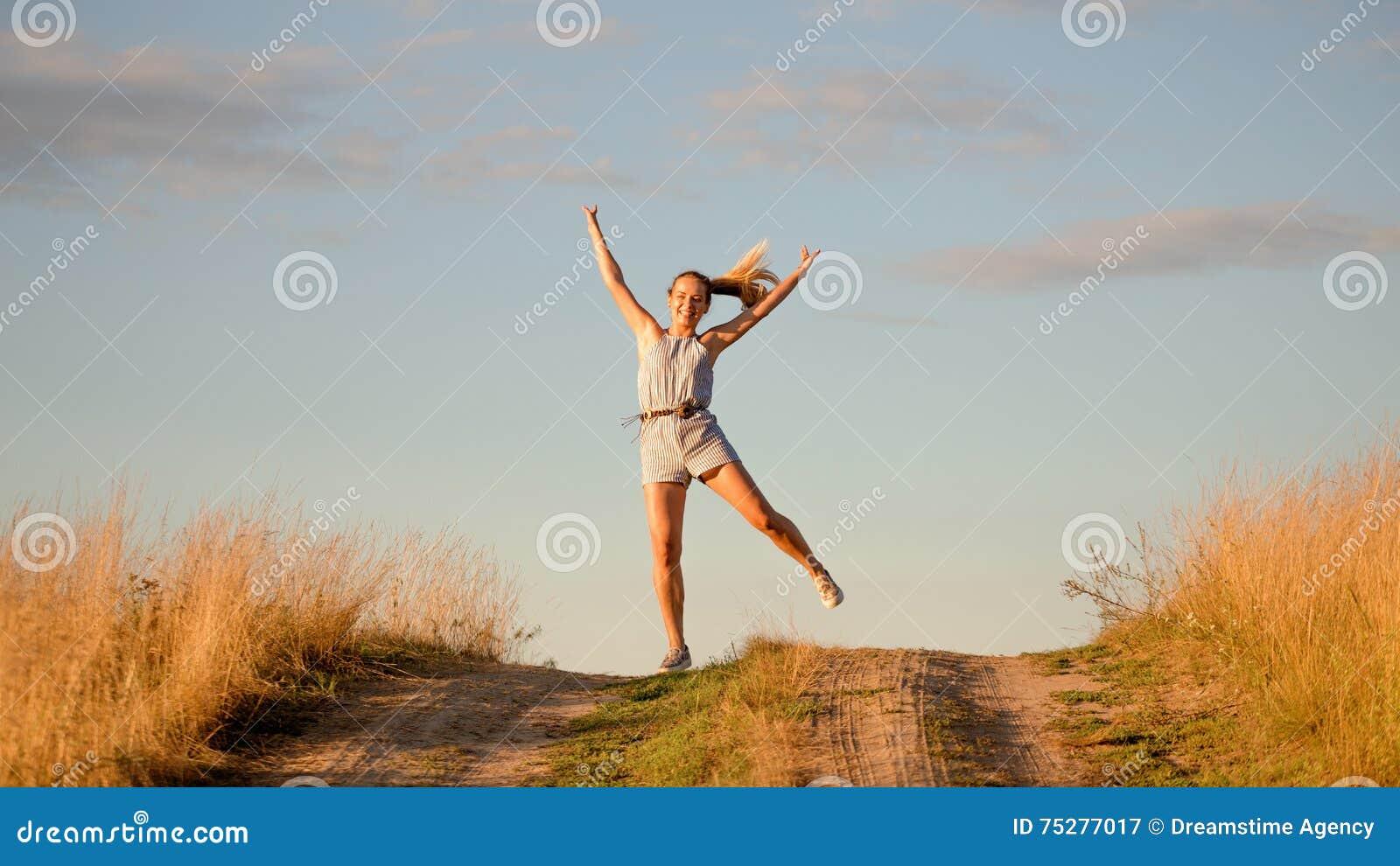 Happy beautiful young girl dancing in a field