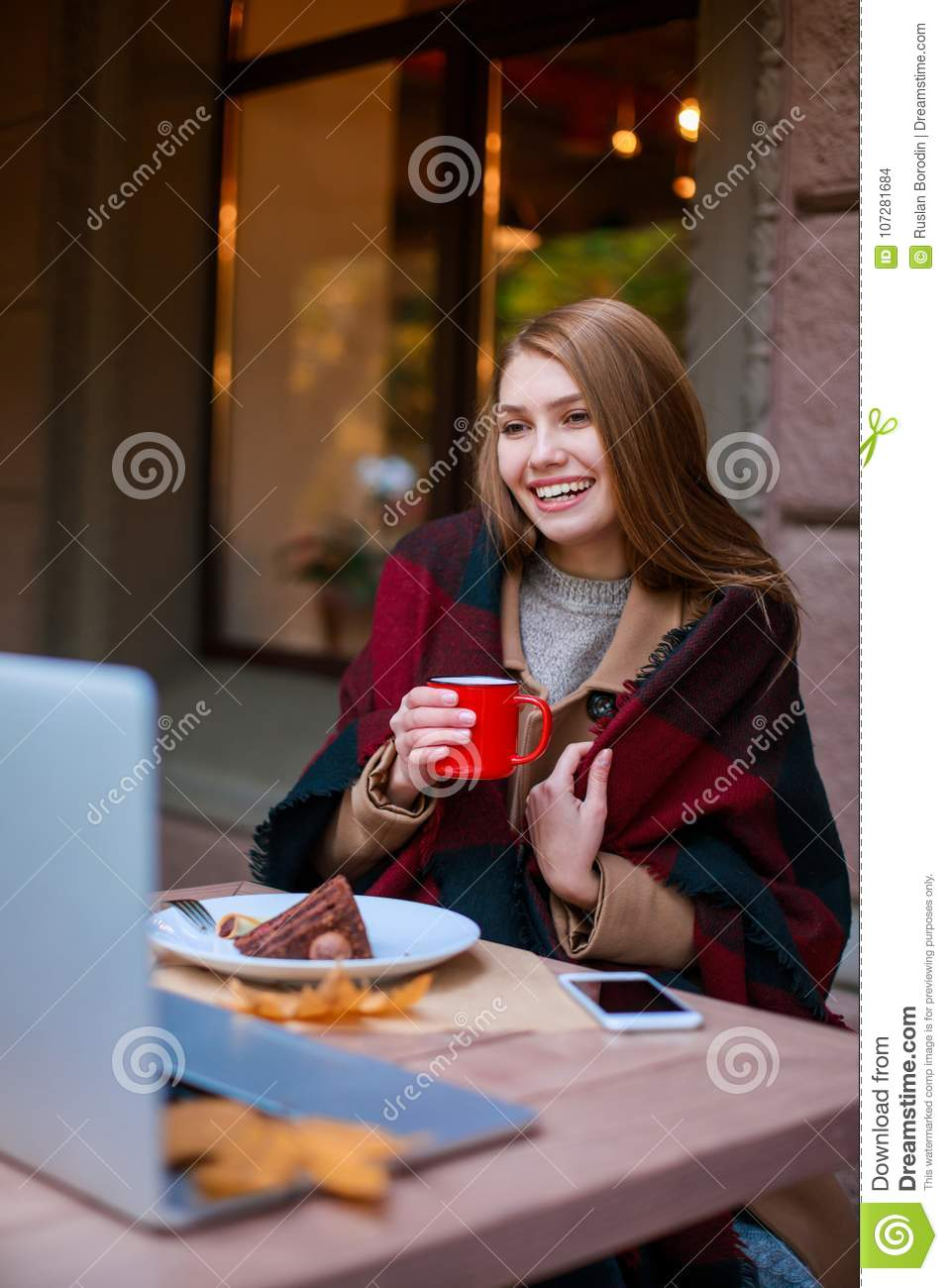 A happy girl, wrapped in a blanket, sits in a cafe talking to someone on a laptop, eating a dessert and drinking from a