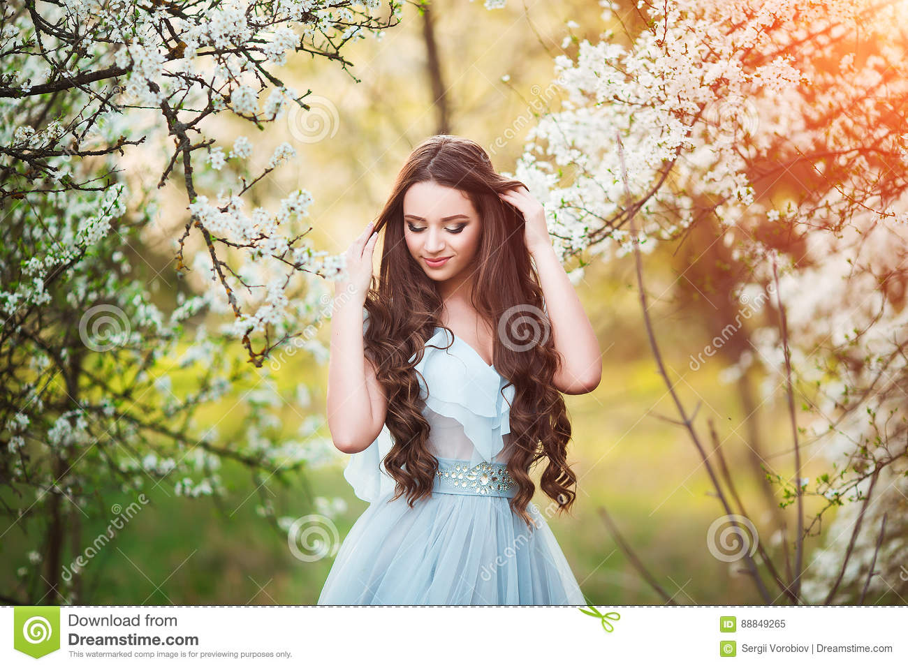 Happy beautiful young woman with long black healthy hair enjoy fresh  flowers and sun light in blossom park at sunset d28b35cfd