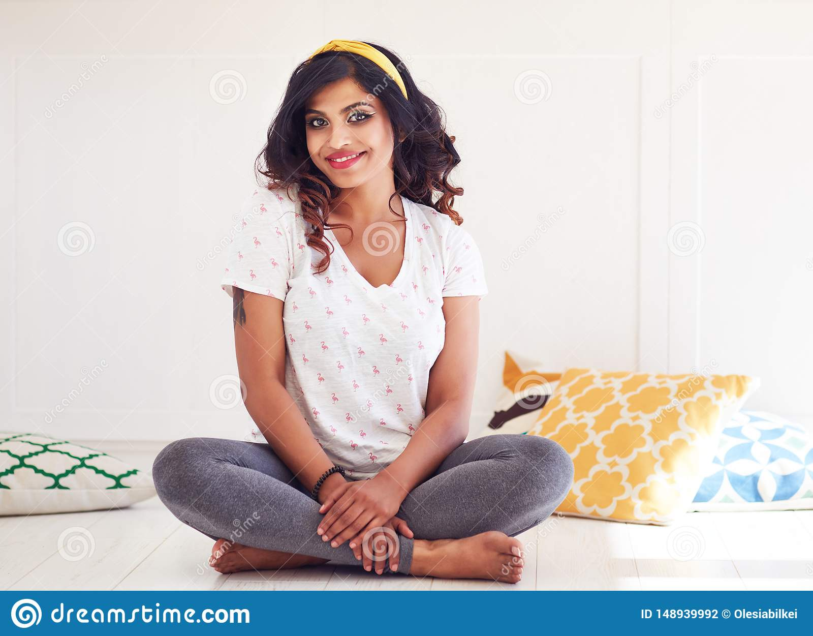 Happy and beautiful young woman sitting on the floor, ready for yoga class