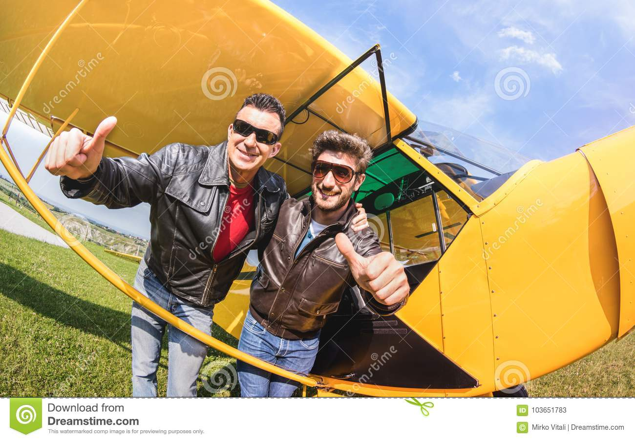 Happy best friends taking selfie at aeroclub with ultra light airplane