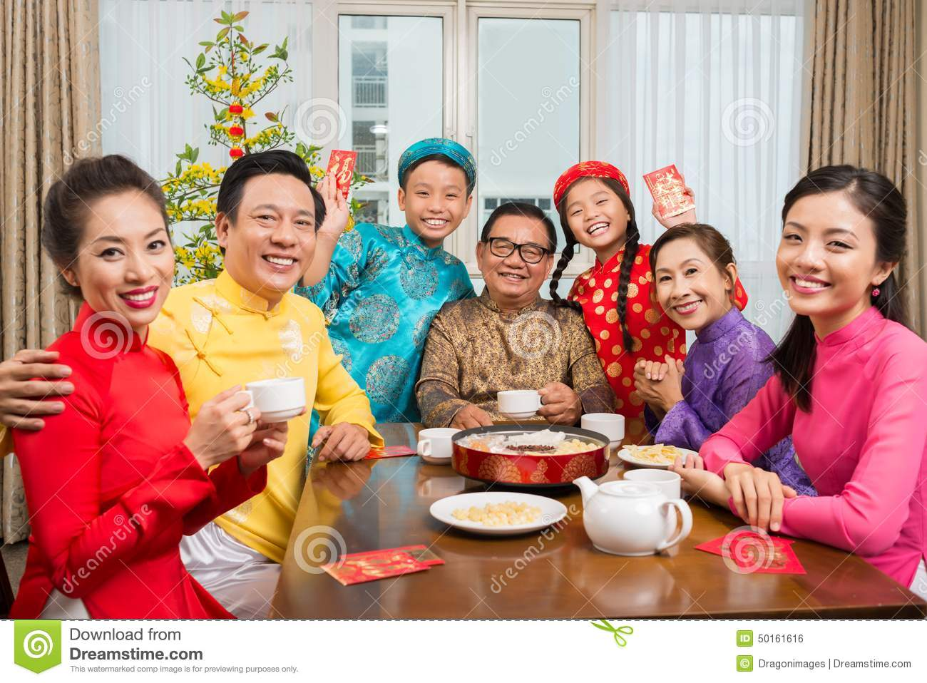 happy-big-vietnamese-family-traditional-costumes-sitting-table-looking-camera-50161616.jpg