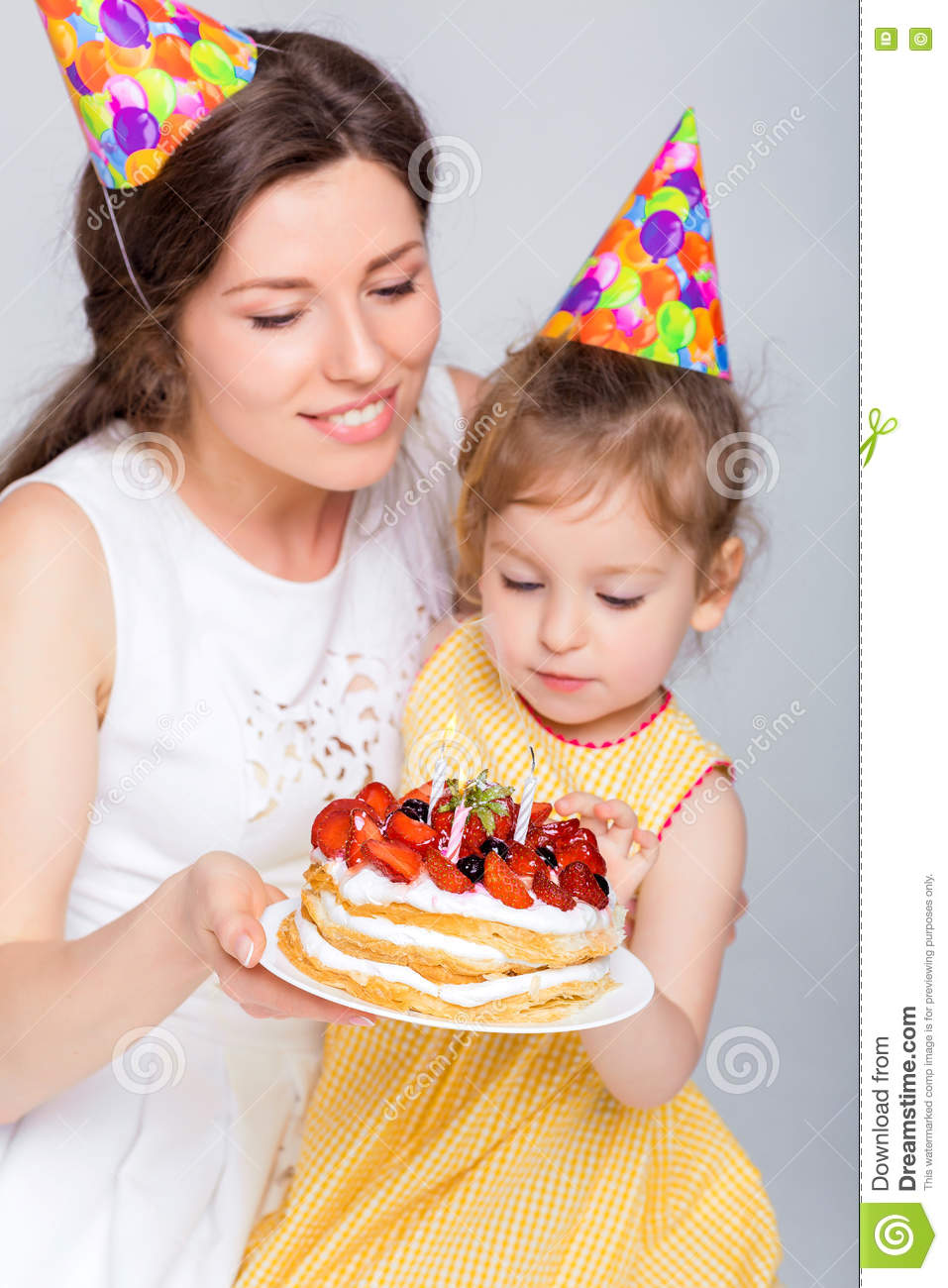 Young Beautiful Mother And Her Little Daughter Are Celebrating A Birthday Cake With Candles Mom Blowing On