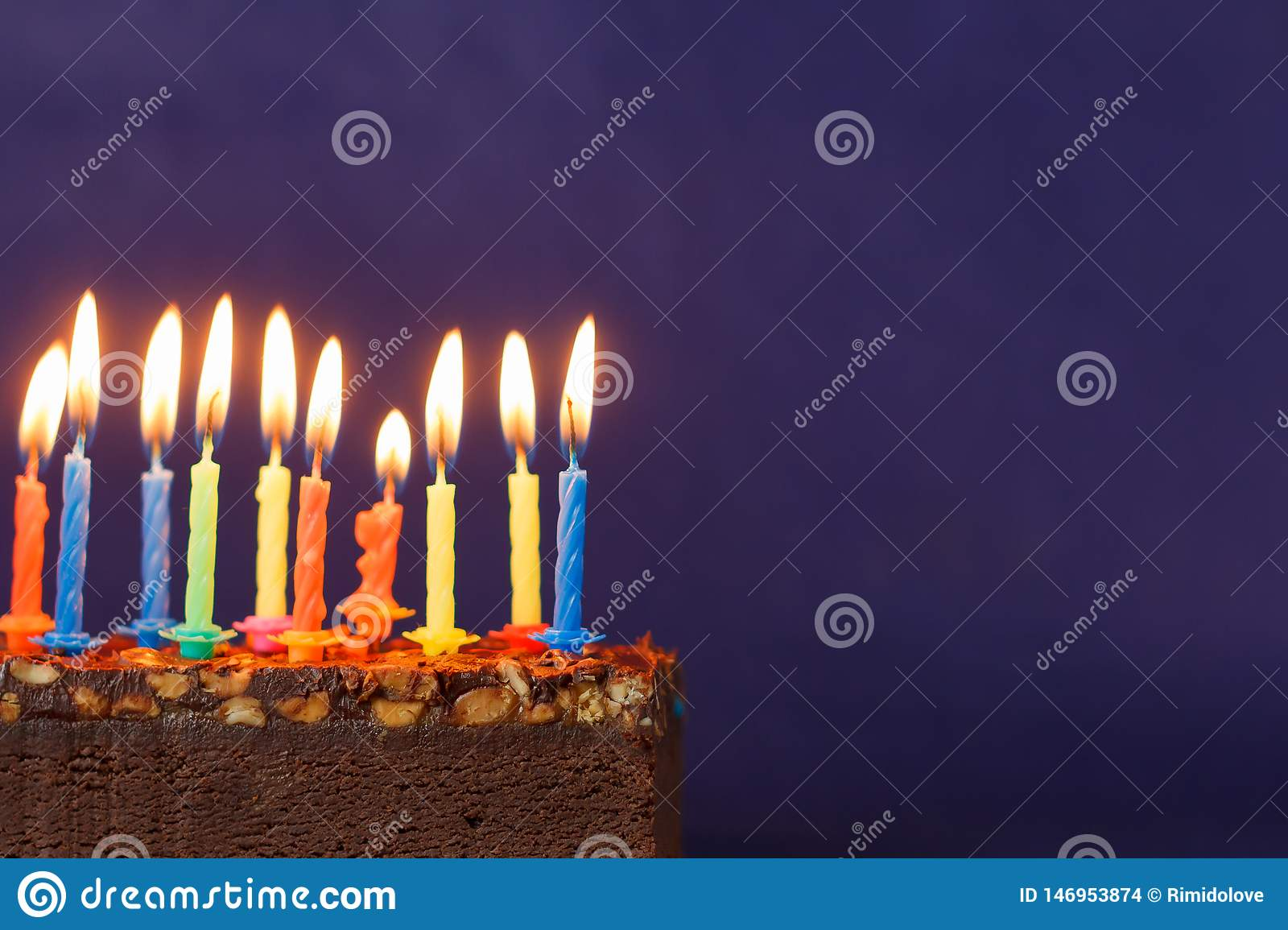 Happy Birthday Brownie Cake with Peanuts, Salted Caramel and Colorful Burning Candles on the Violet Background. Copy Space for