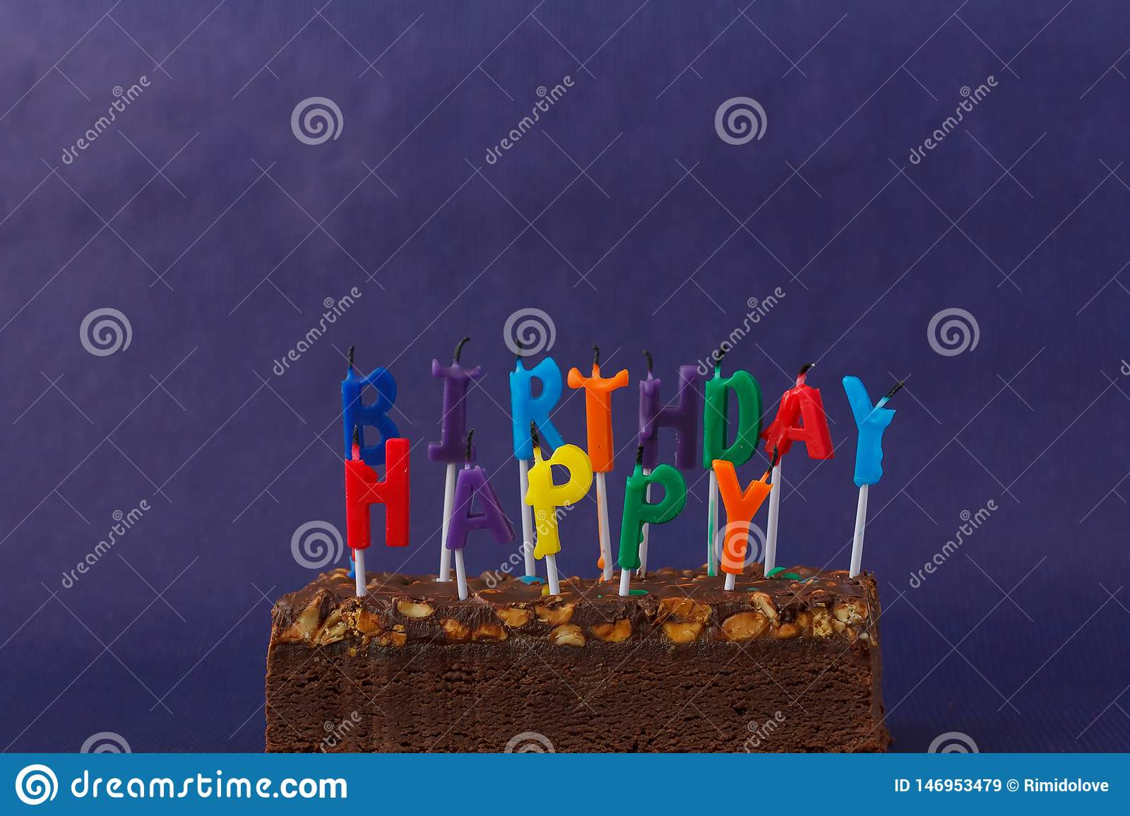 Happy Birthday Brownie Cake with Peanuts, Salted Caramel and Colorful Unlighted Candles on the Violet Background. Copy Space for