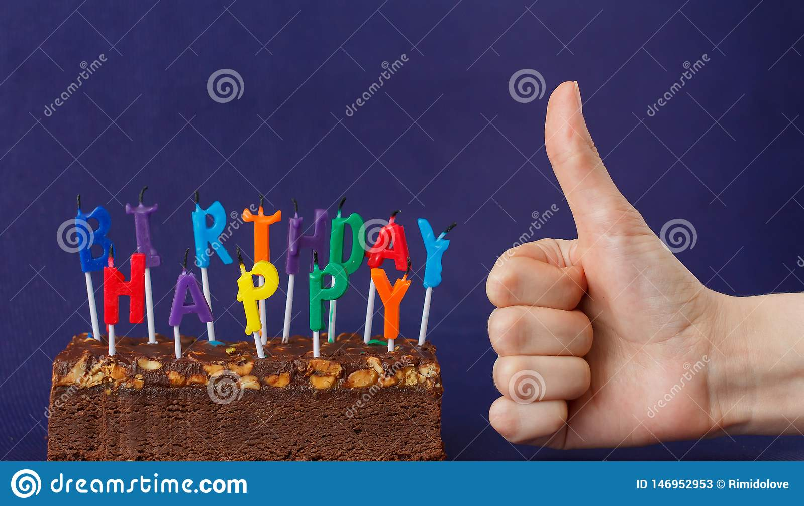 Happy Birthday Brownie Cake with Peanuts, Salted Caramel and Colorful Unlighted Candles on the Violet Background. Hand Shows Like
