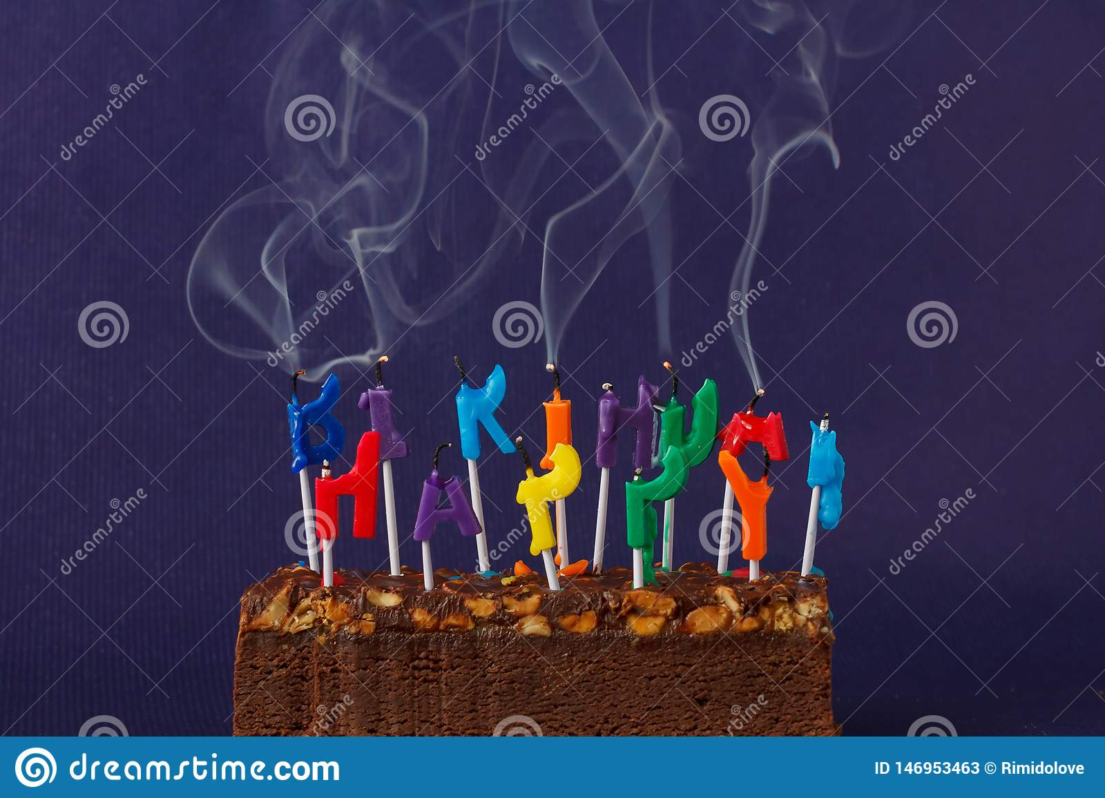 Happy Birthday Brownie Cake with Peanuts, Salted Caramel and Colorful Unlighted Smoking Candles on the Violet Background. Copy
